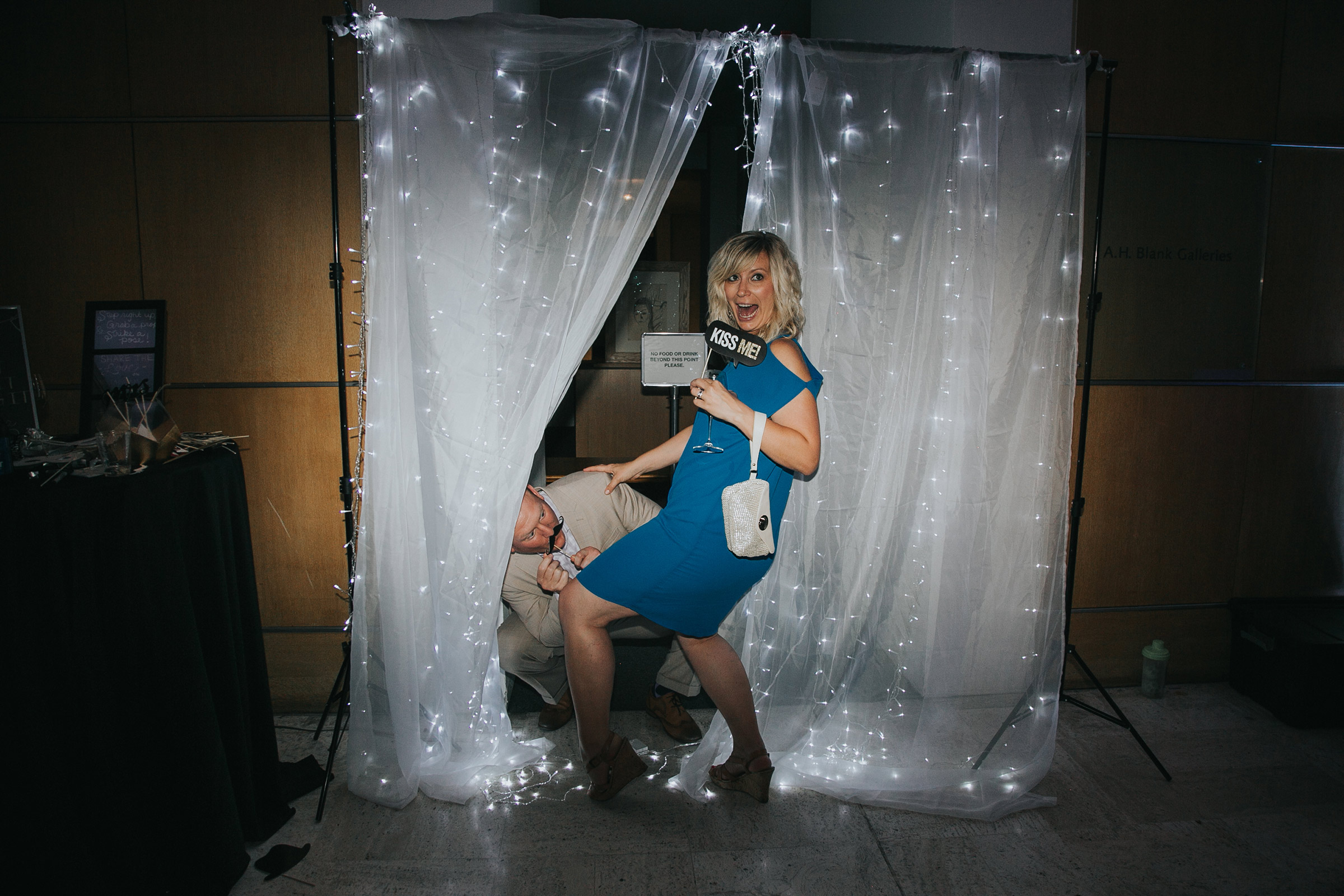 guest-in-photobooth-being-funny-with-signs-desmoines-iowa-art-center-raelyn-ramey-photography.jpg
