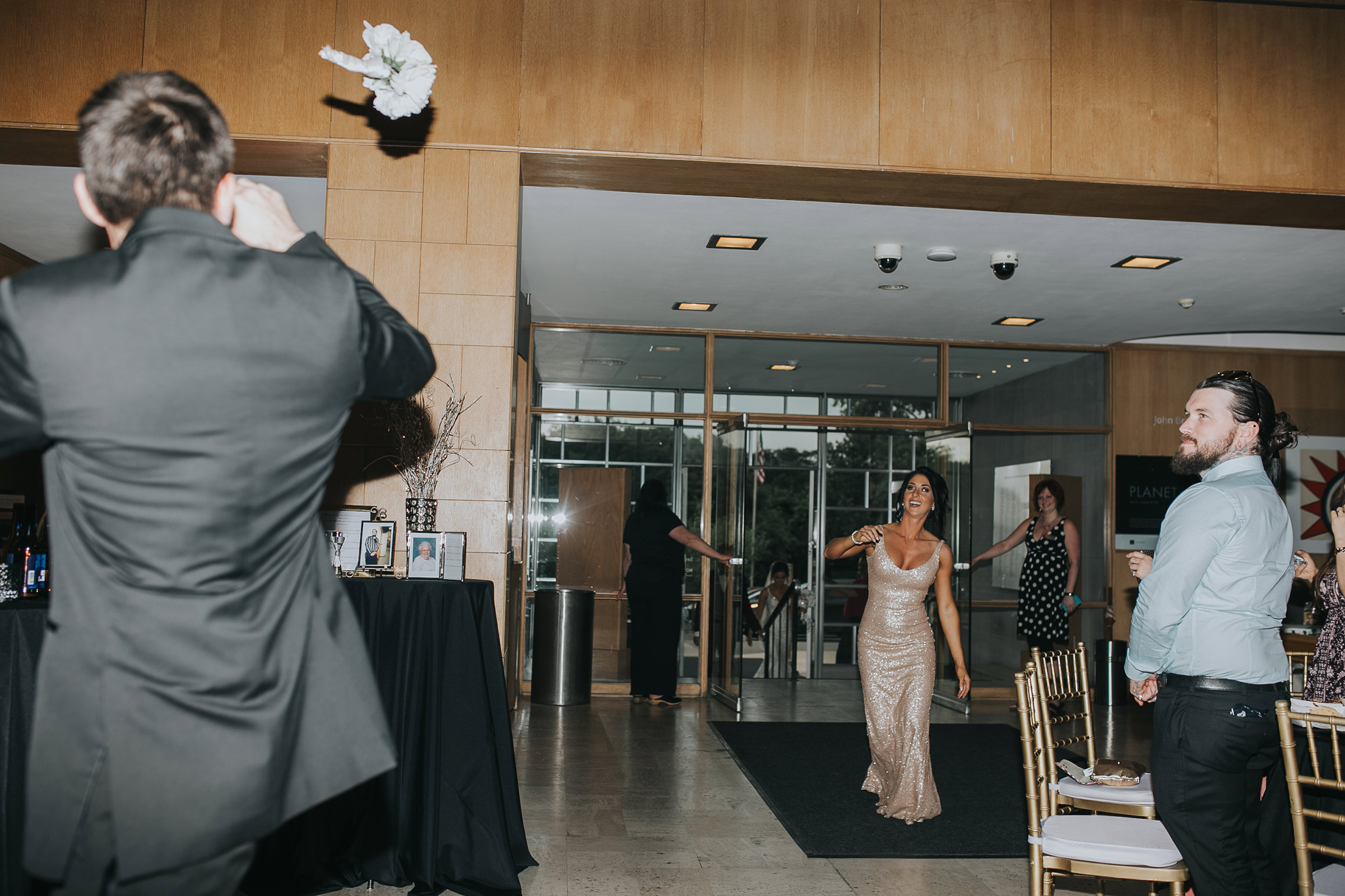 maid-of-honor-throwing-bouquet-grand-enterance-desmoines-iowa-art-center-raelyn-ramey-photography.jpg