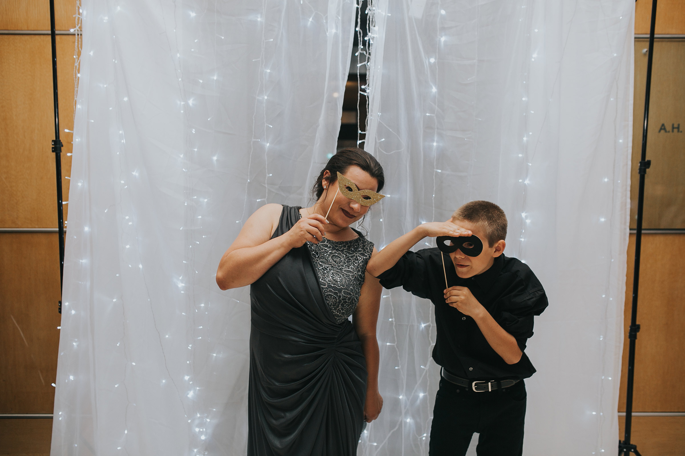 mom-guest-and-son-posing-with-photobooth-props-desmoines-iowa-art-center-raelyn-ramey-photography.jpg