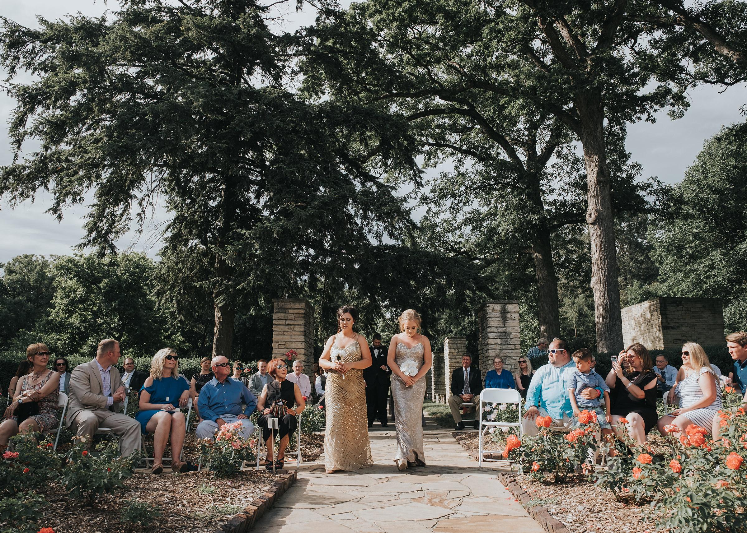 personal-attendants-walking-down-aisle-desmoines-iowa-rose-garden-raelyn-ramey-photography.jpg