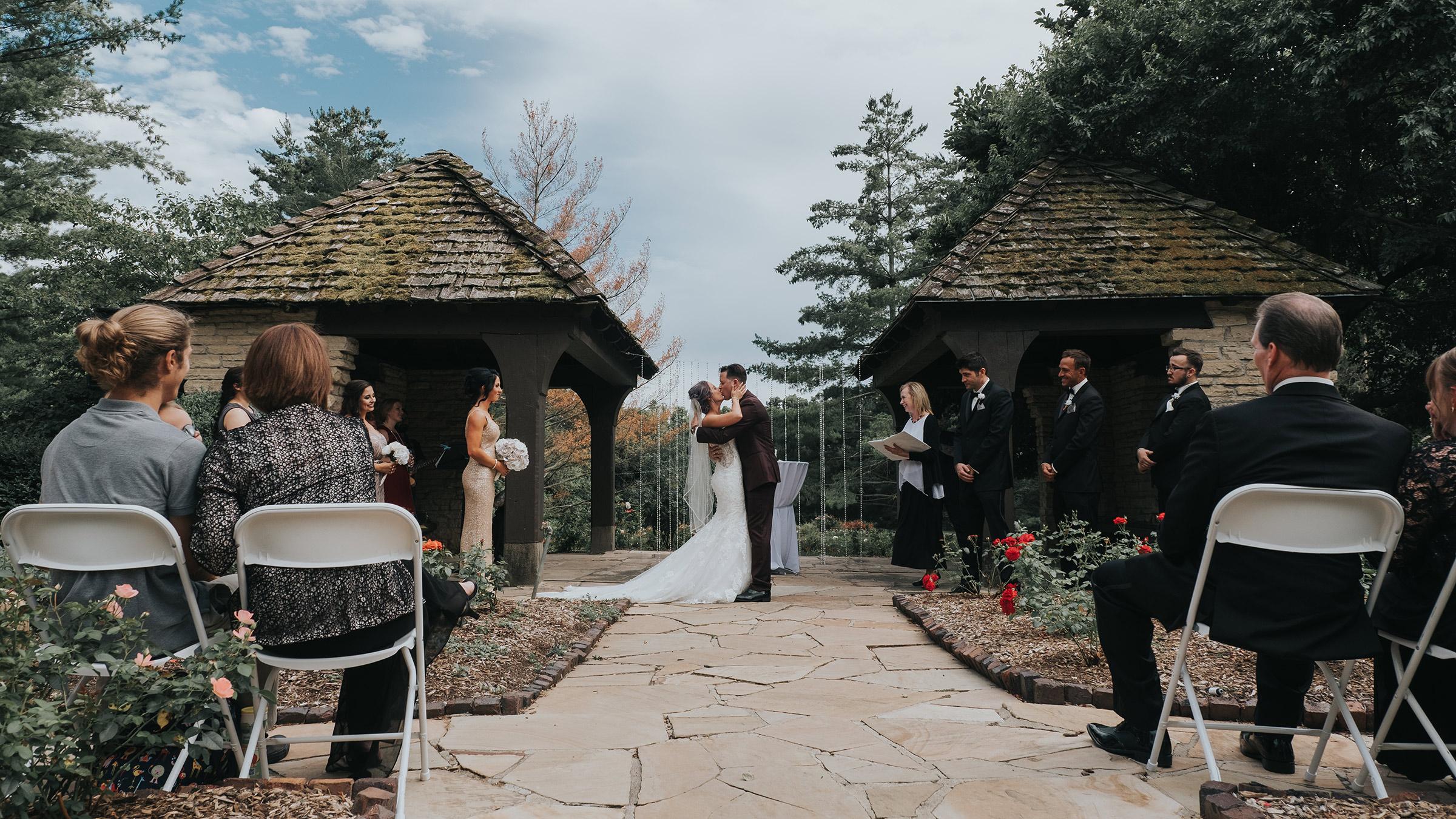 wedding-couple-first-kiss-at-ceremony-desmoines-iowa-rose-garden-raelyn-ramey-photography.jpg
