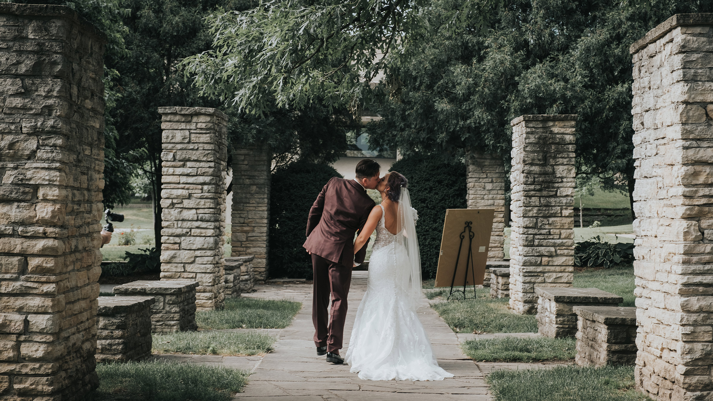 wedding-couple-kissing-at-end-of-aisle-desmoines-iowa-rose-garden-raelyn-ramey-photography.jpg