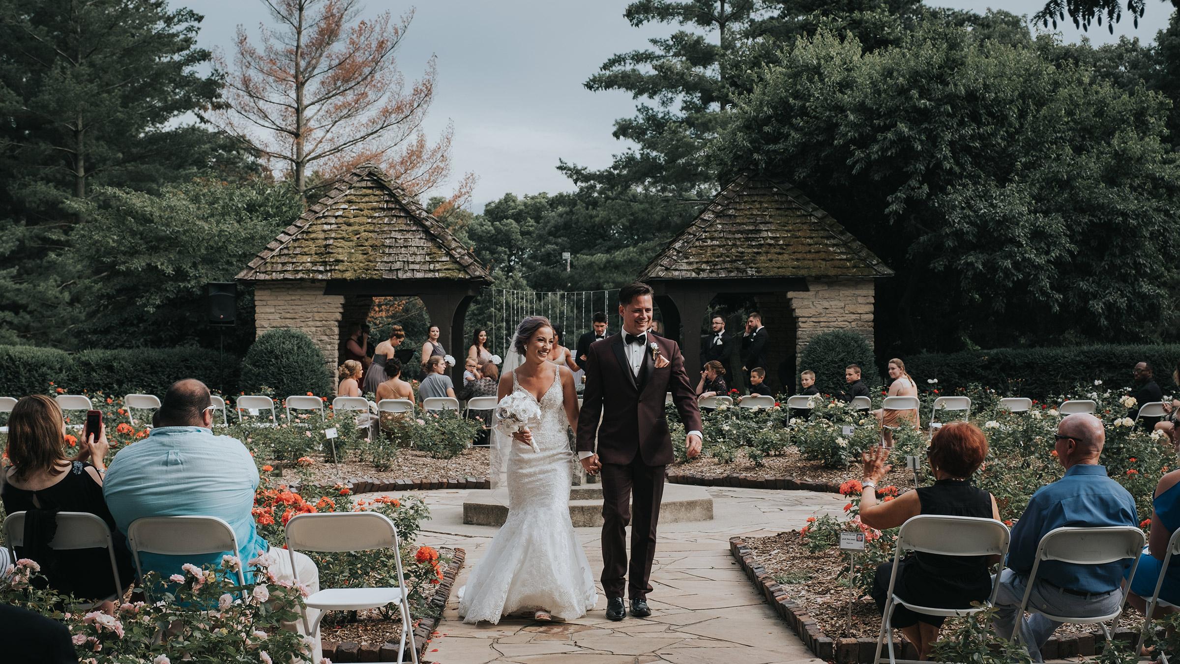wedding-couple-walking-down-aisle-after-ceremony-desmoines-iowa-rose-garden-raelyn-ramey-photography.jpg