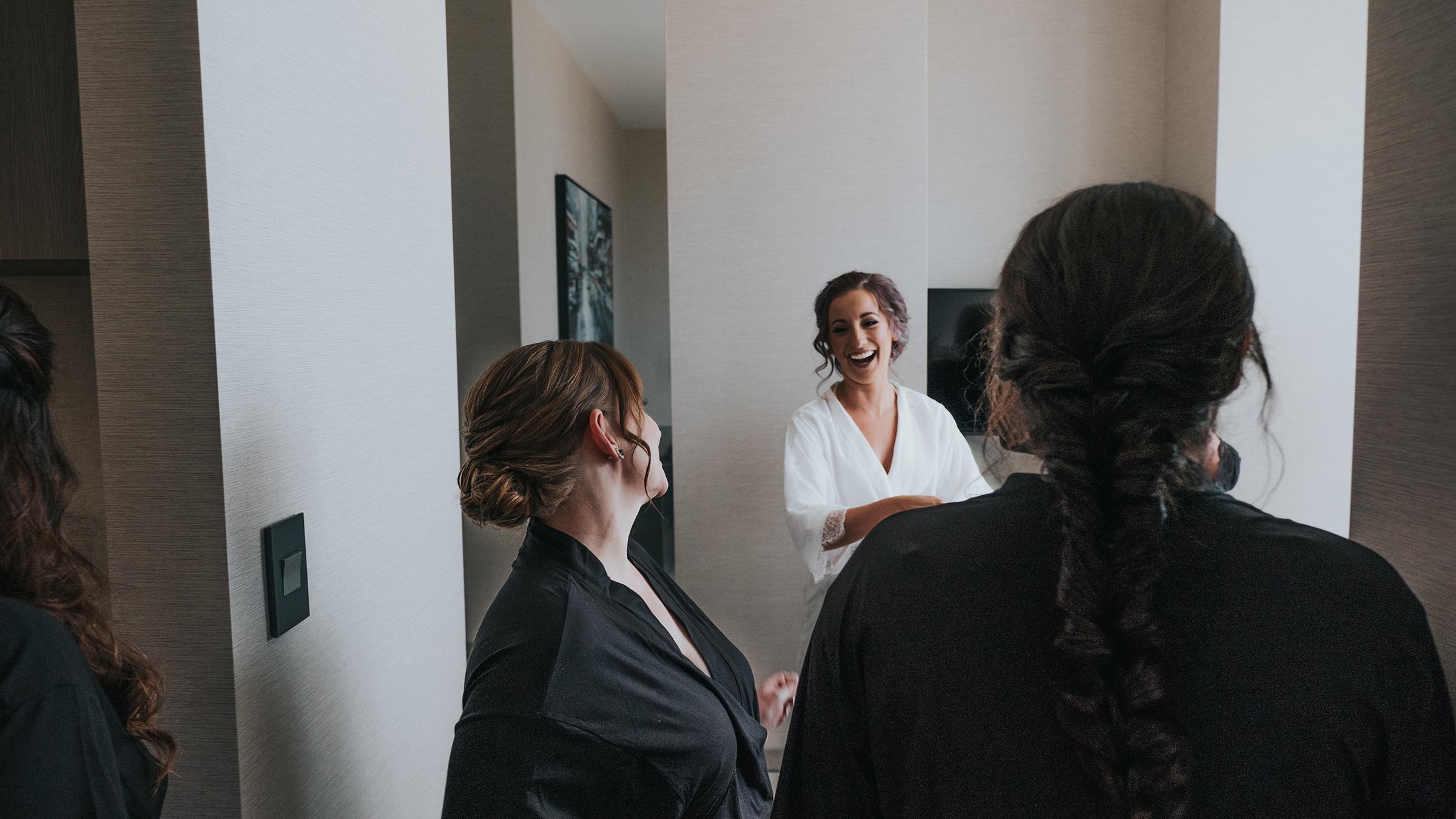 bride-laughing-getting-ready-ac-hotel-desmoines-iowa-raelyn-ramey-photography.jpg