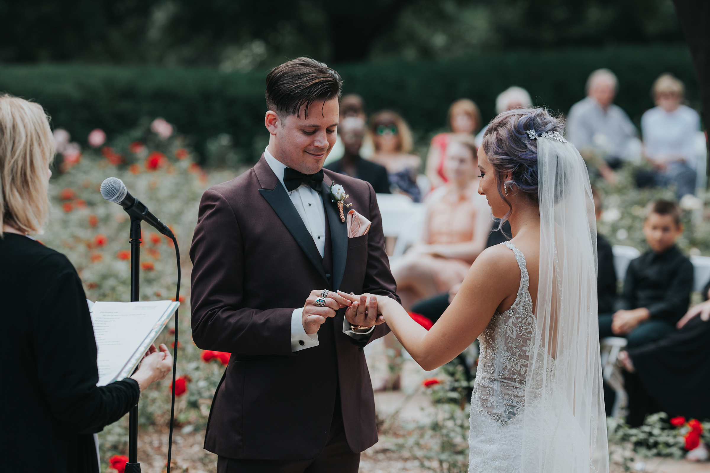 groom-putting-ring-on-bride-during-ceremony-rose-garden-raelyn-ramey-photography.jpg