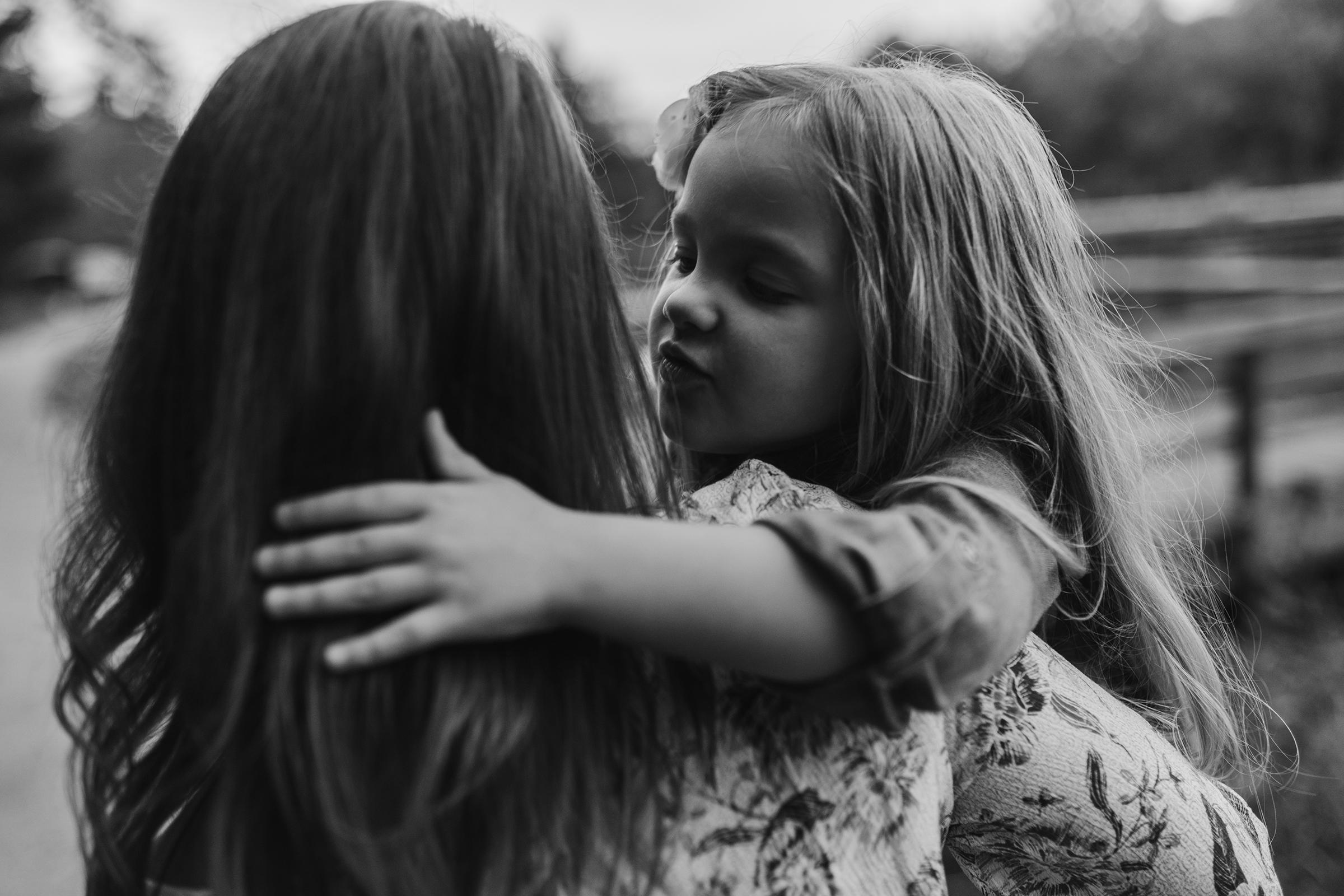 mueller-family-child-kissing-and-holding-mom-granger-iowa-raelyn-ramey-photography.jpg