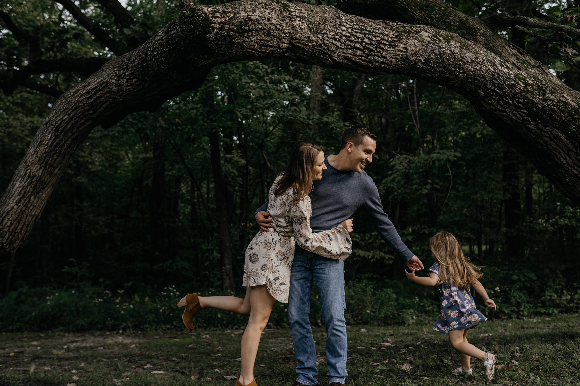 mueller-family-daughter-running-around-parents-granger-iowa-raelyn-ramey-photography.jpg