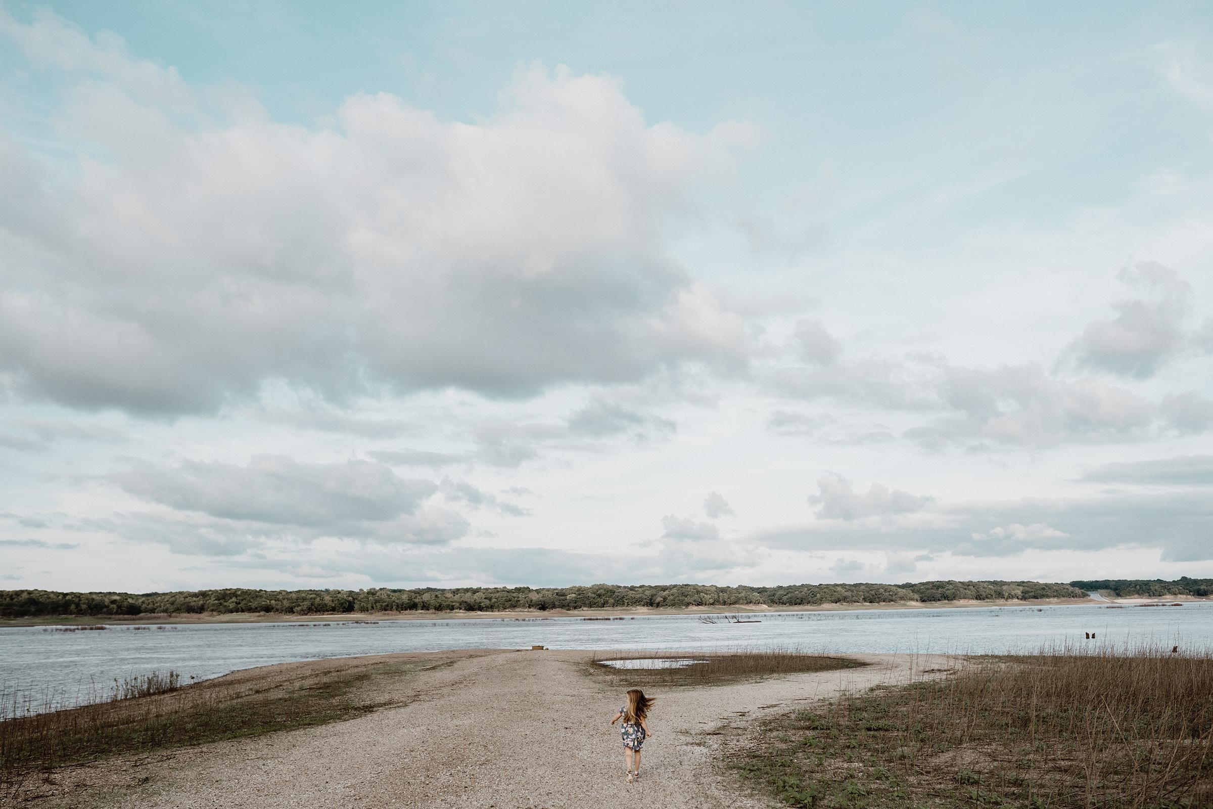 mueller-family-daughter-running-toward-water-granger-iowa-raelyn-ramey-photography.jpg