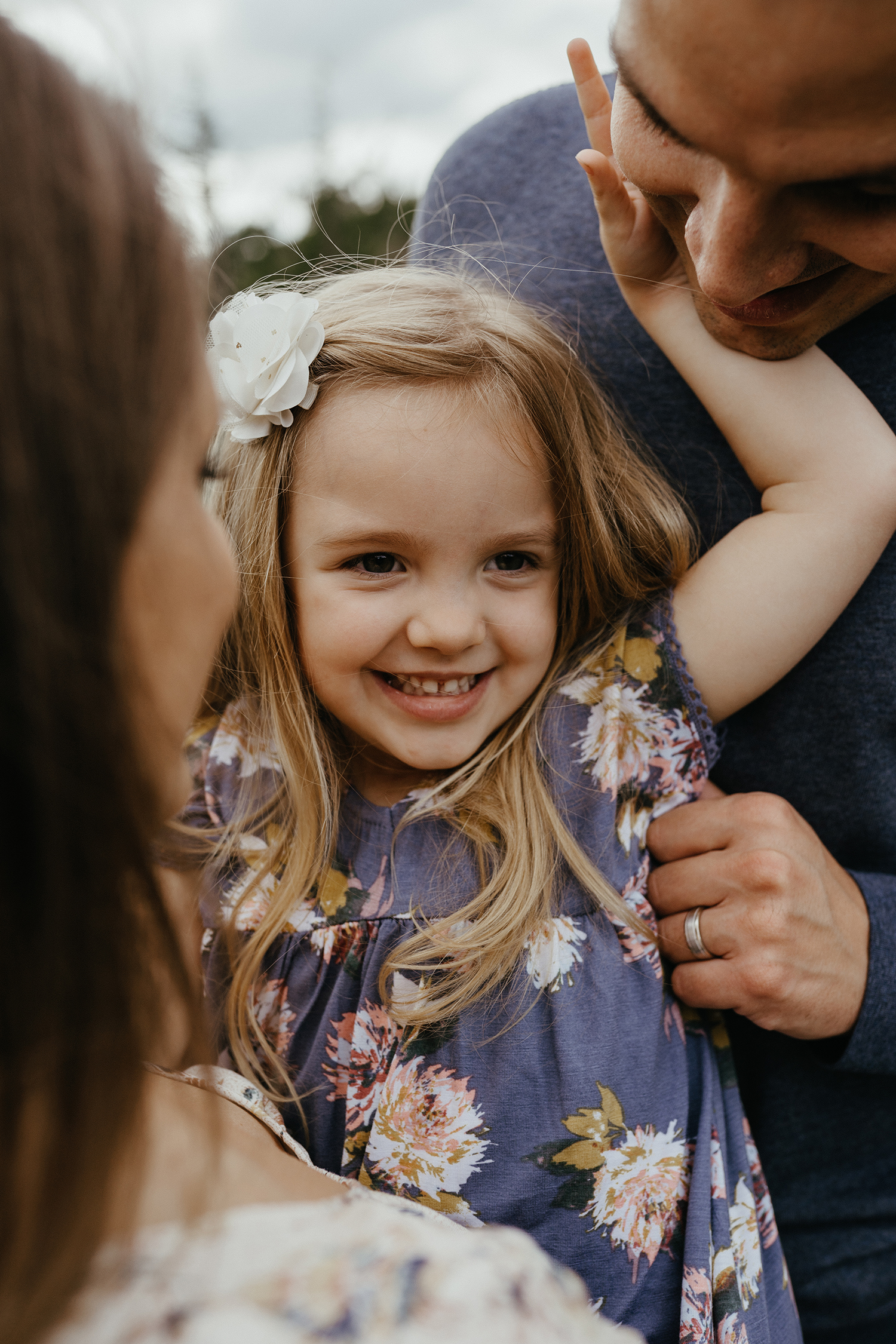 mueller-family-parents-holding-daughter-and-smiling-granger-iowa-raelyn-ramey-photography.jpg