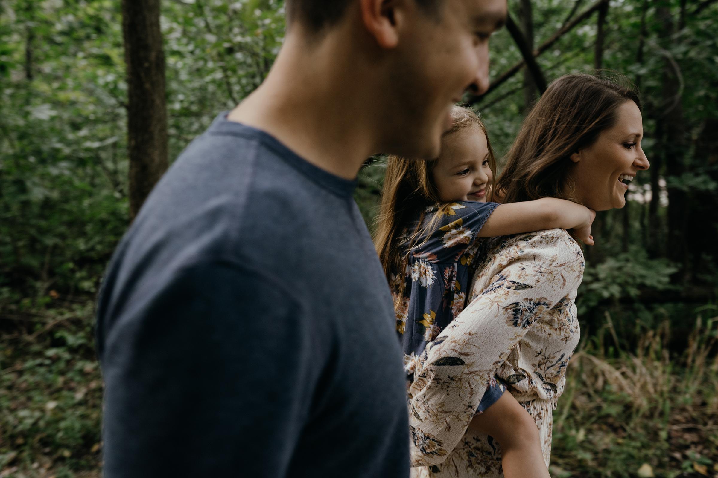mueller-family-walking-with-child-on-back-of-mom-granger-iowa-raelyn-ramey-photography.jpg