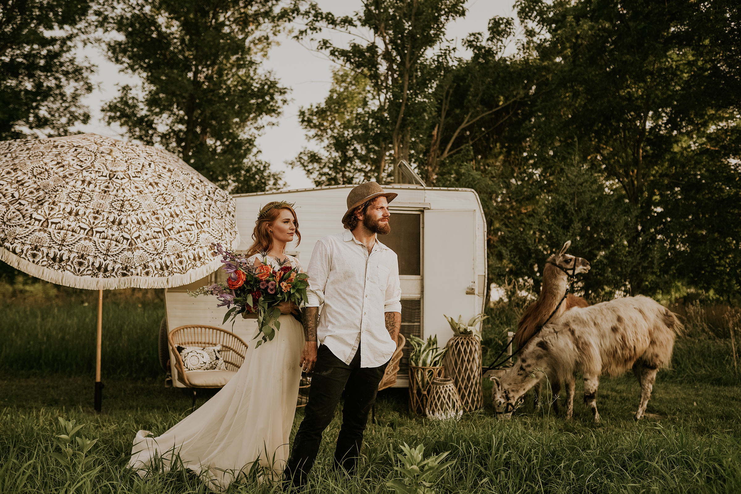 bride-groom-standing-in-front-of-camper-looking-out-myrtle-mae-iris-aisle-dame-maiden-lavender-blue-floral-raelyn-ramey-photography.jpg
