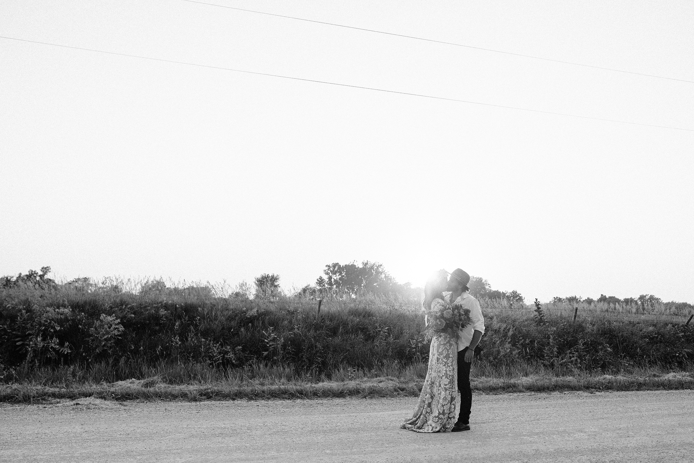 bride-kissing-groom-in-road-myrtle-mae-iris-aisle-dame-maiden-lavender-blue-floral-raelyn-ramey-photography.jpg