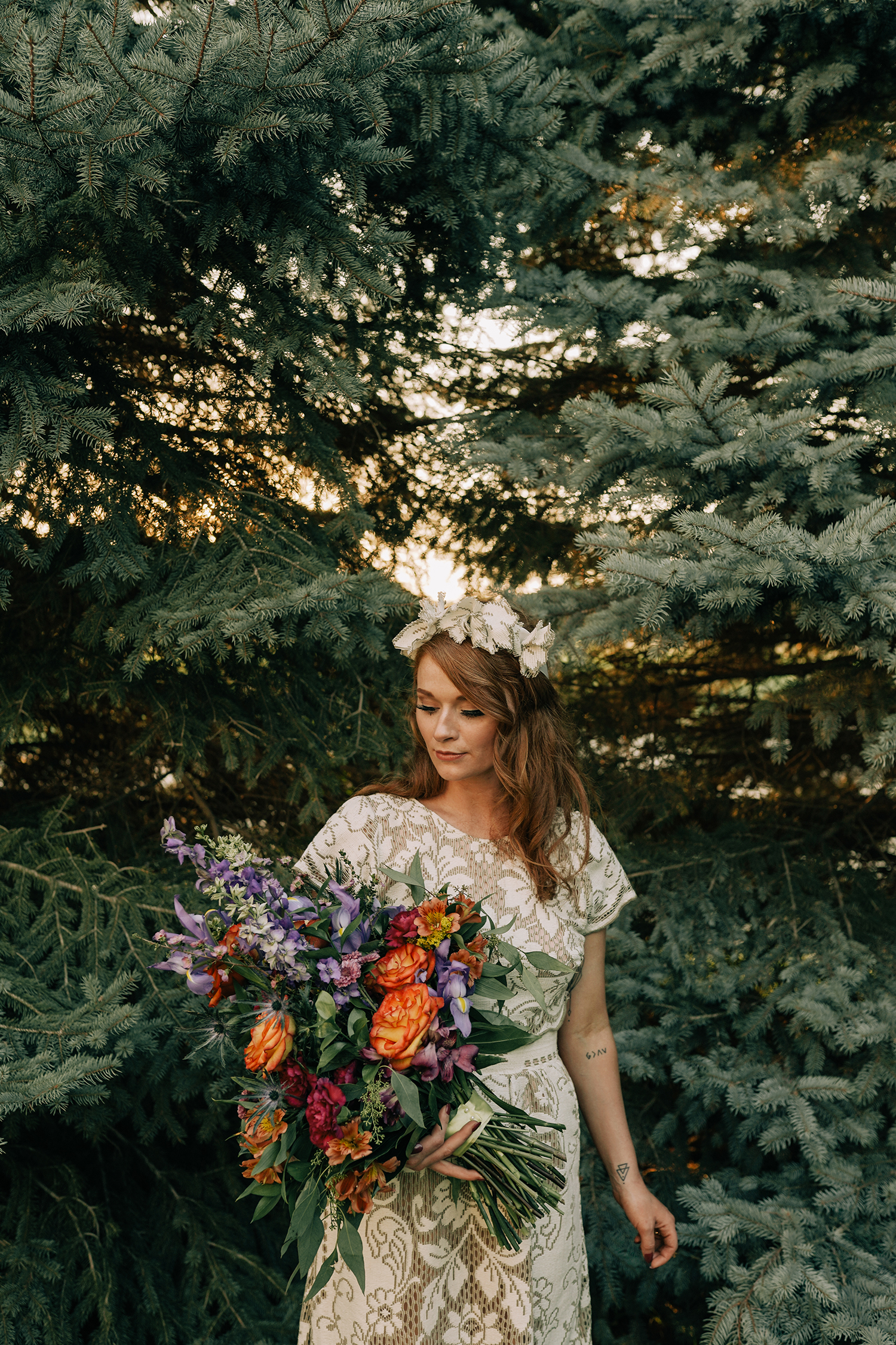 bride-standing-in-front-of-pine-trees-with-bouquet-myrtle-mae-iris-aisle-dame-maiden-lavender-blue-floral-raelyn-ramey-photography.jpg