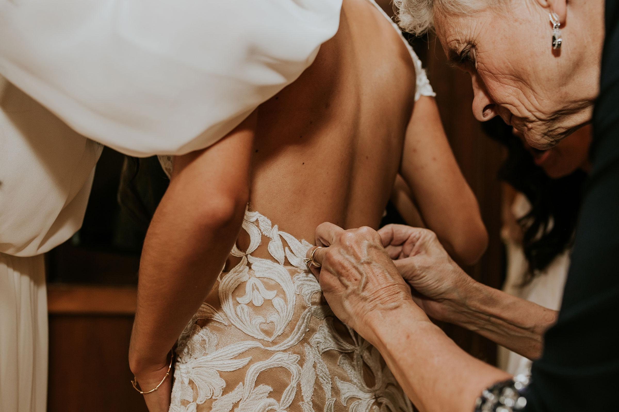 bride-getting-dress-on-hilton-omaha-nebraska-raelyn-ramey-photography.jpg