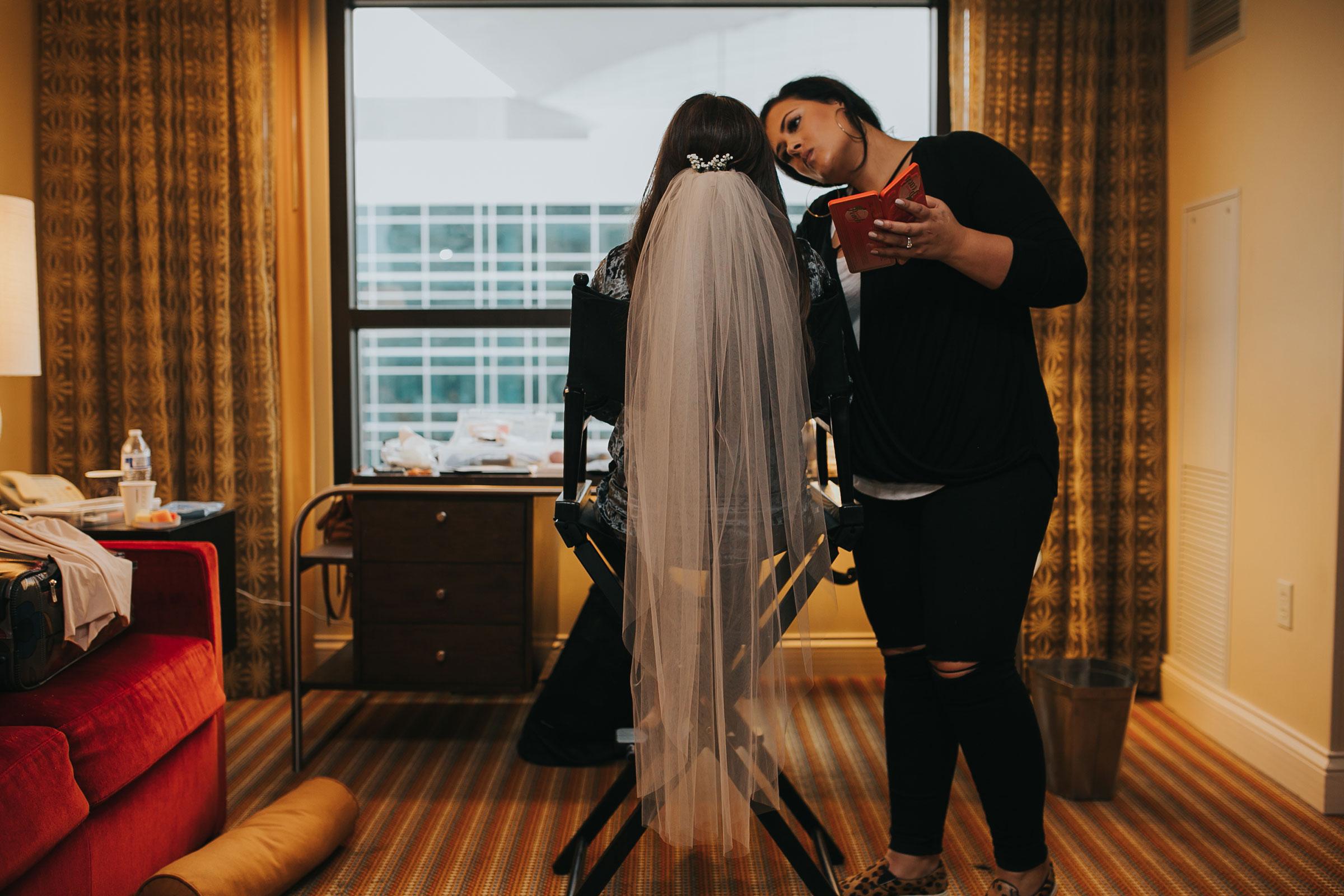bride-getting-makeup-on-while-wearing-veil-hilton-omaha-nebraska-raelyn-ramey-photography.jpg