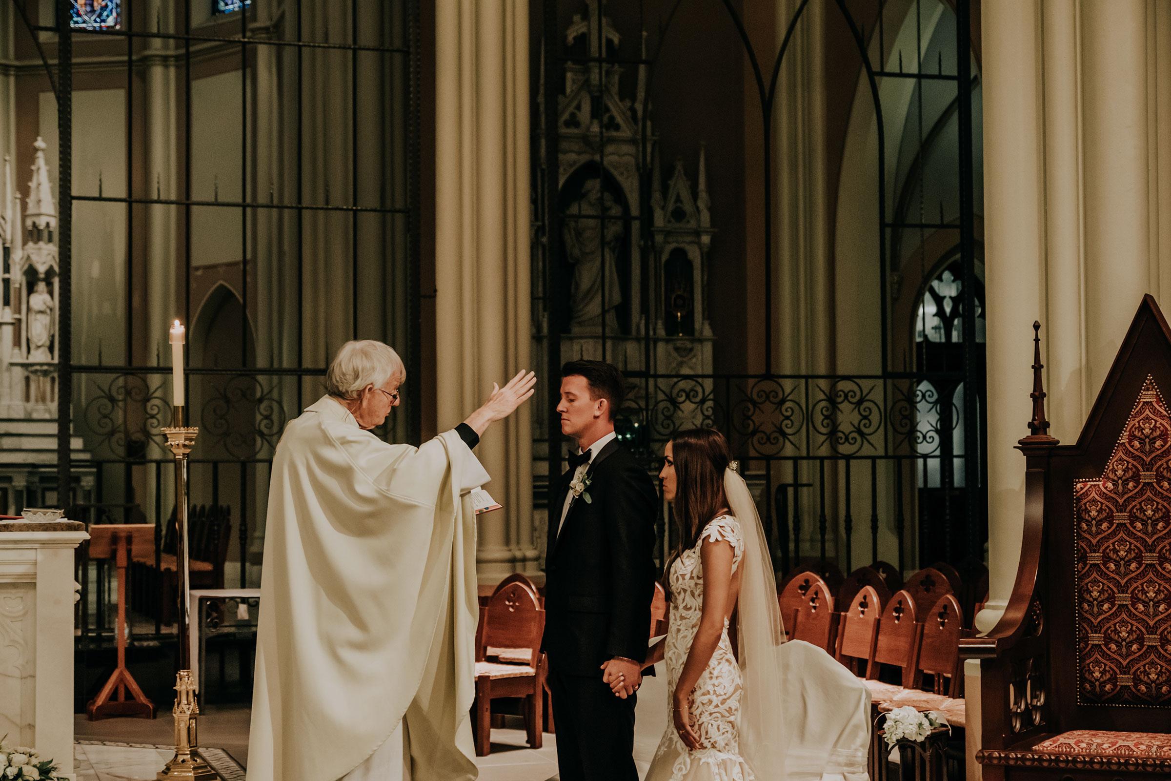 bride-groom-being-blessed-at-ceremony-st-johns-church-at-creighton-omaha-nebraska-raelyn-ramey-photography.jpg