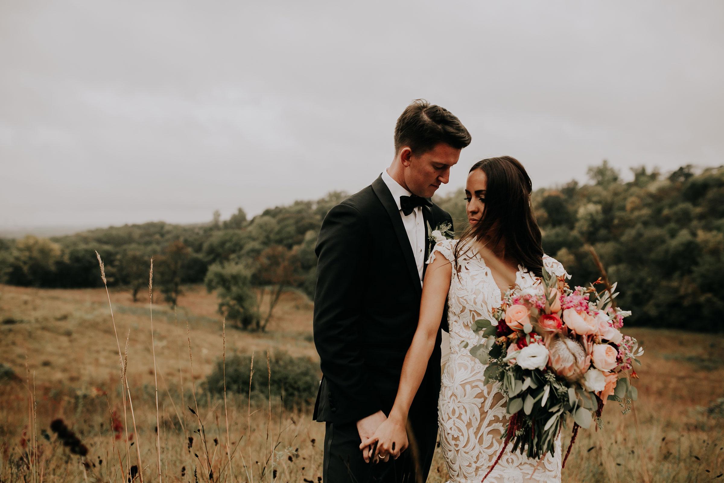 bride-groom-holding-hands-on-hill-top-omaha-nebraska-raelyn-ramey-photography.jpg