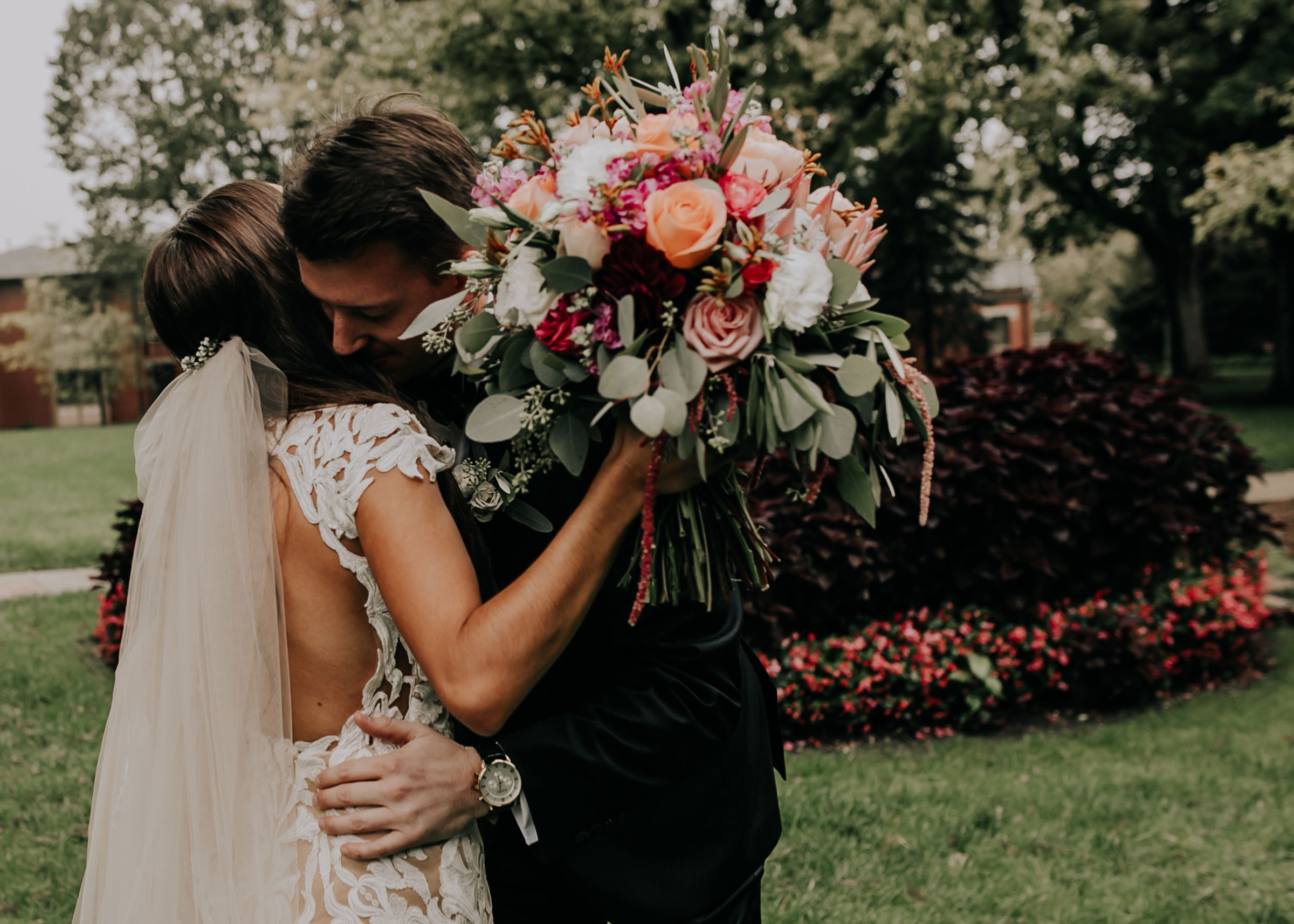 bride-groom-hug-during-first-look-st-johns-church-at-creighton-omaha-nebraska-raelyn-ramey-photography.jpg