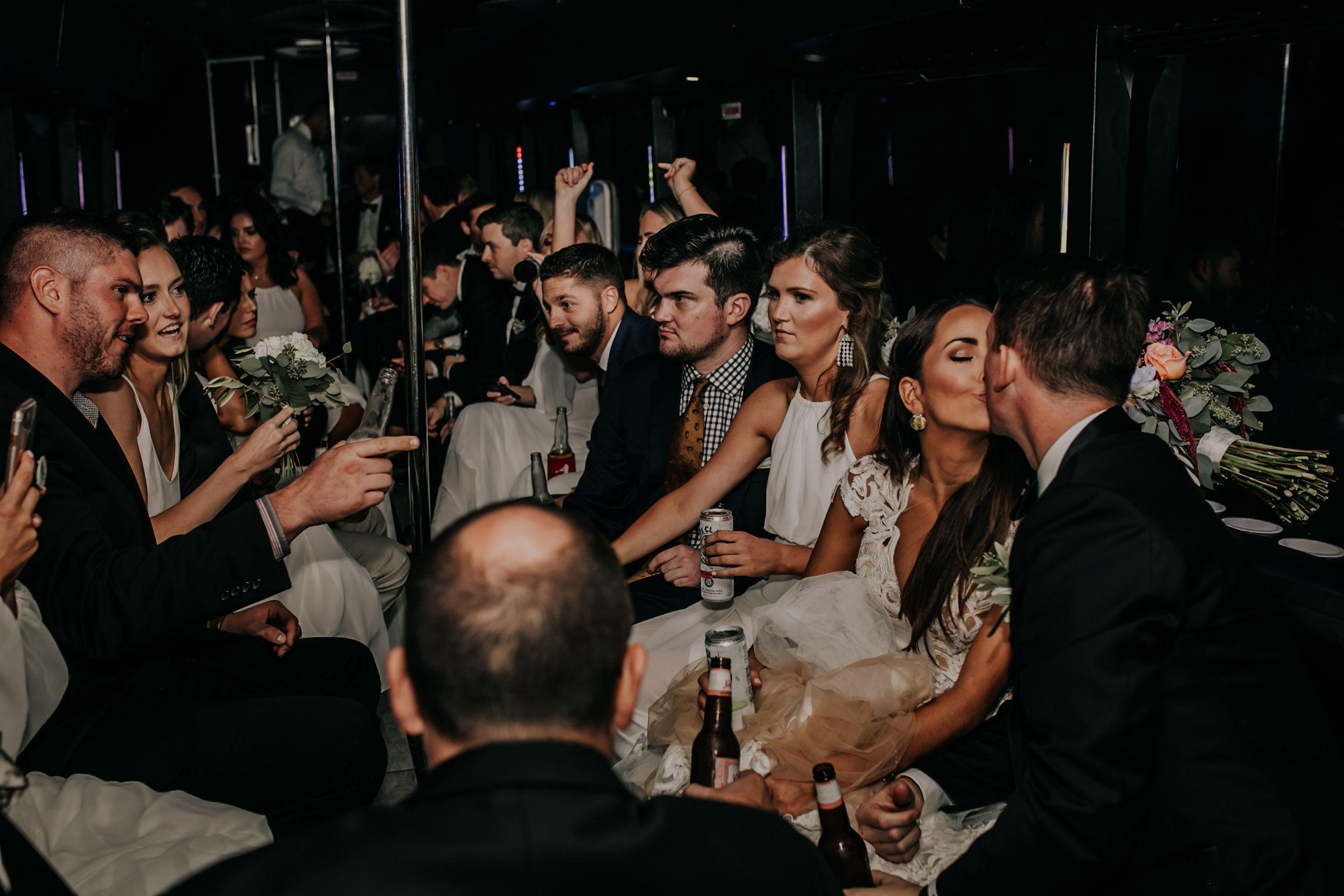 bride-groom-kissing-on-party-bus-omaha-nebraska-raelyn-ramey-photography.jpg