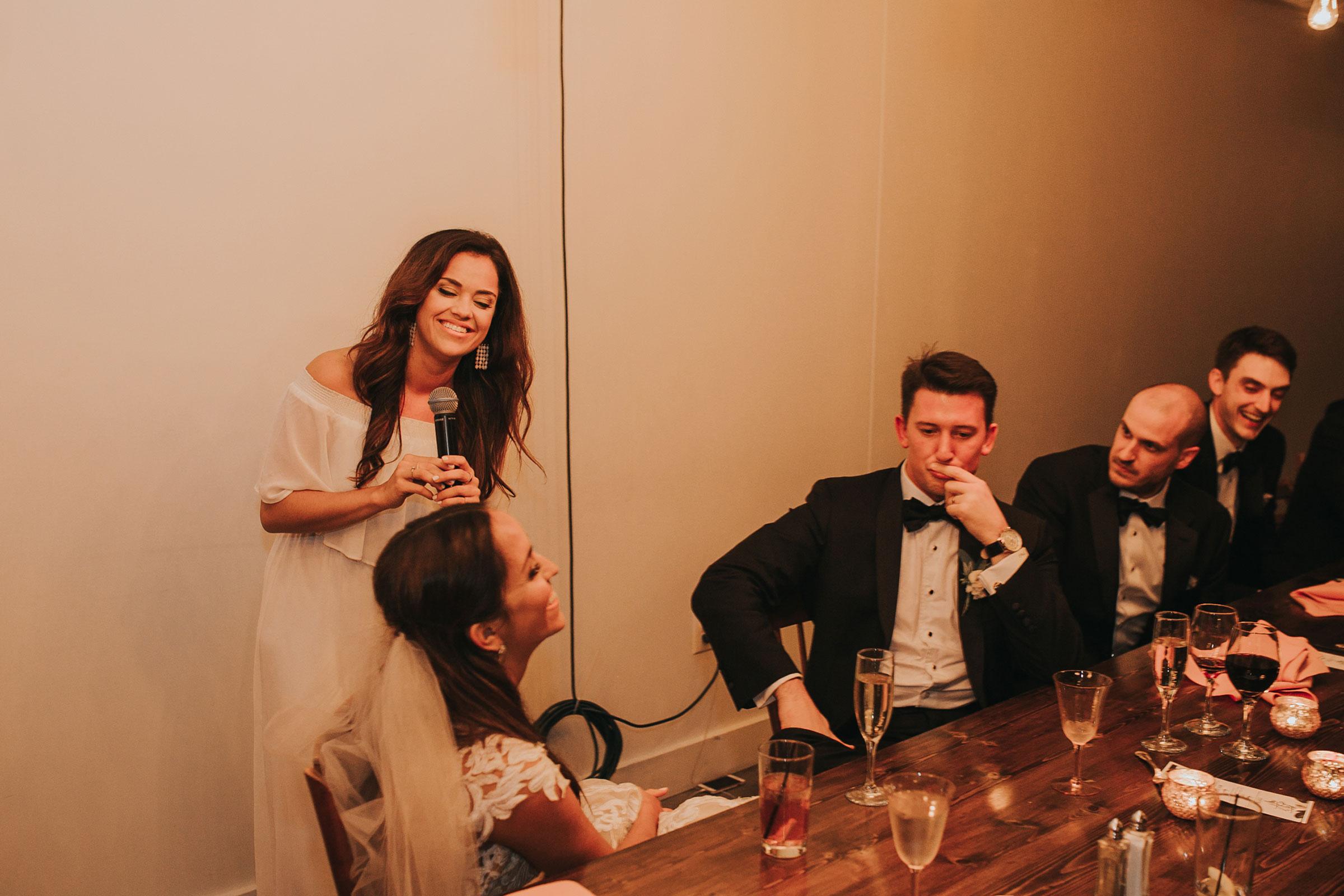 bride-groom-laughing-at-maid-of-honor-speech-omaha-nebraska-raelyn-ramey-photography.jpg