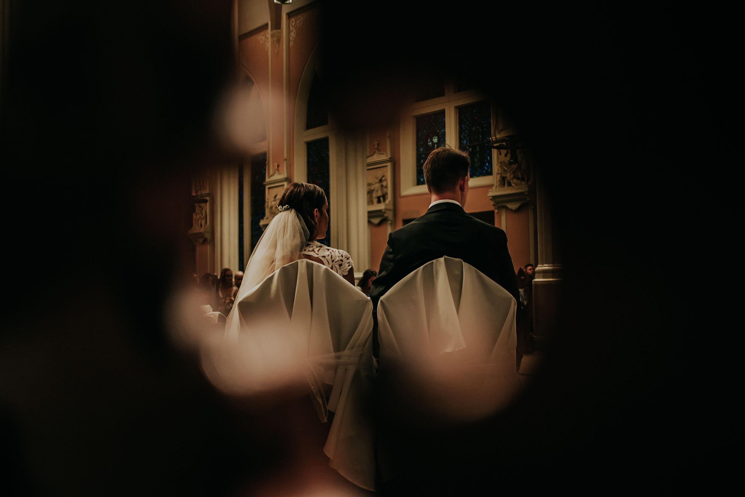 bride-groom-sitting-at-ceremony-st-johns-church-at-creighton-omaha-nebraska-raelyn-ramey-photography.jpg