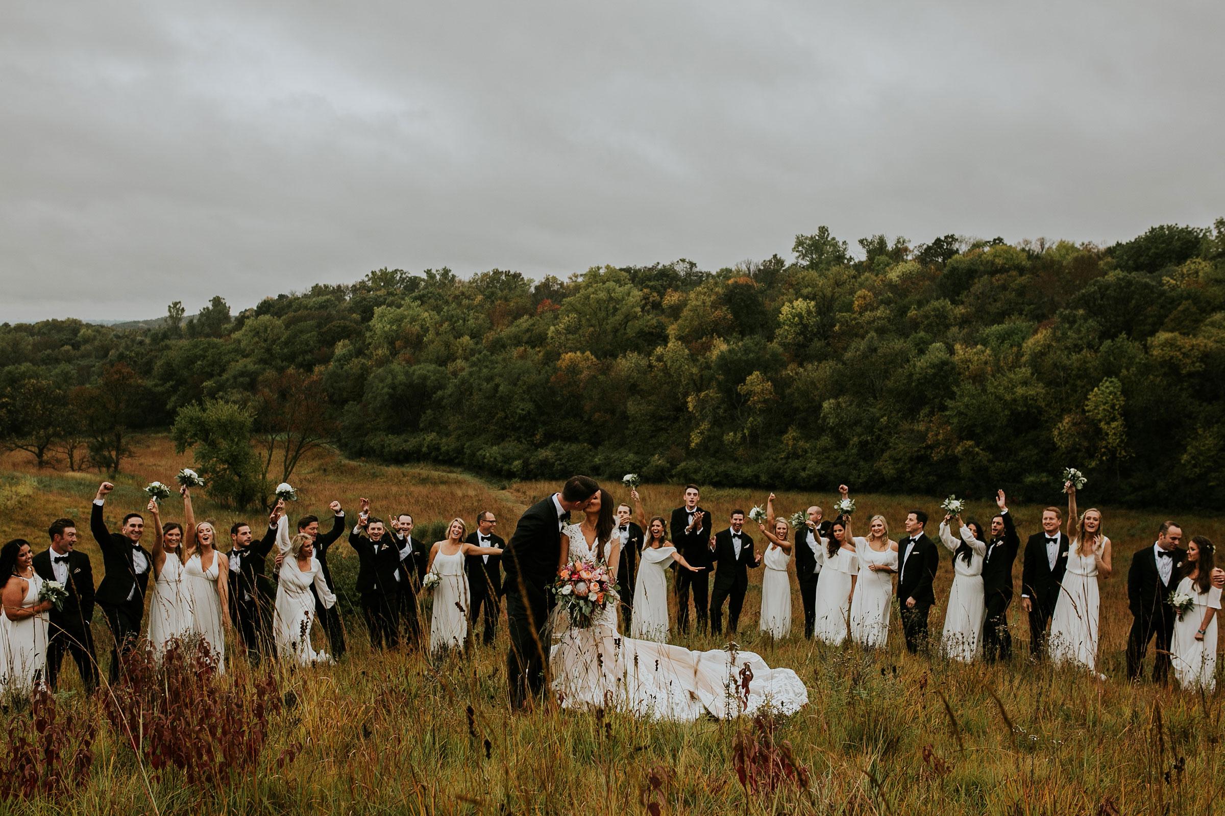 bride-groom-kissing-wedding-party-standing-around-on-hill-top-omaha-nebraska-raelyn-ramey-photography.jpg