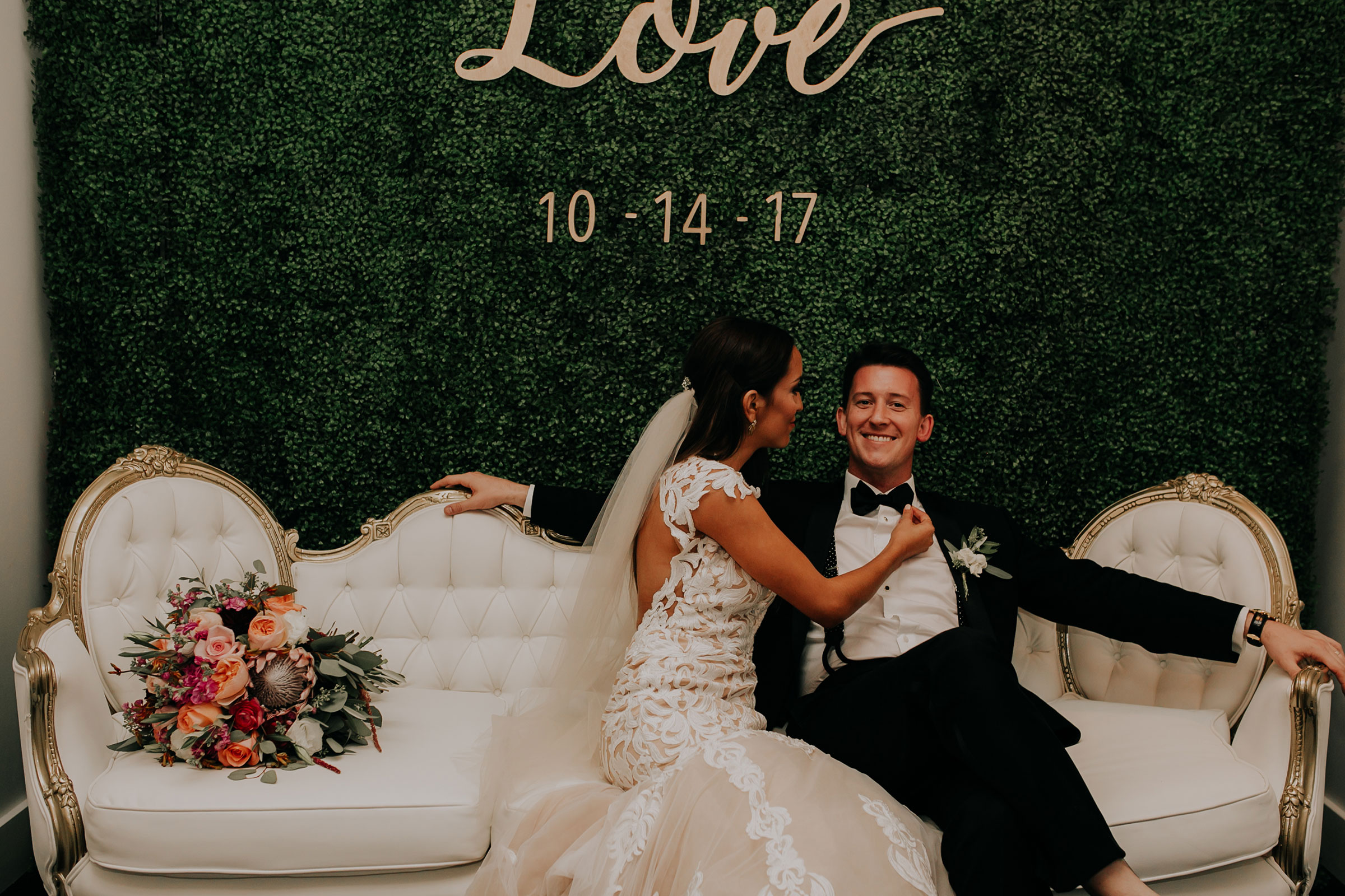 bride-groom-sitting-in-photo-booth-with-victorian-couch-founders-one-nine-omaha-nebraska-raelyn-ramey-photography.jpg