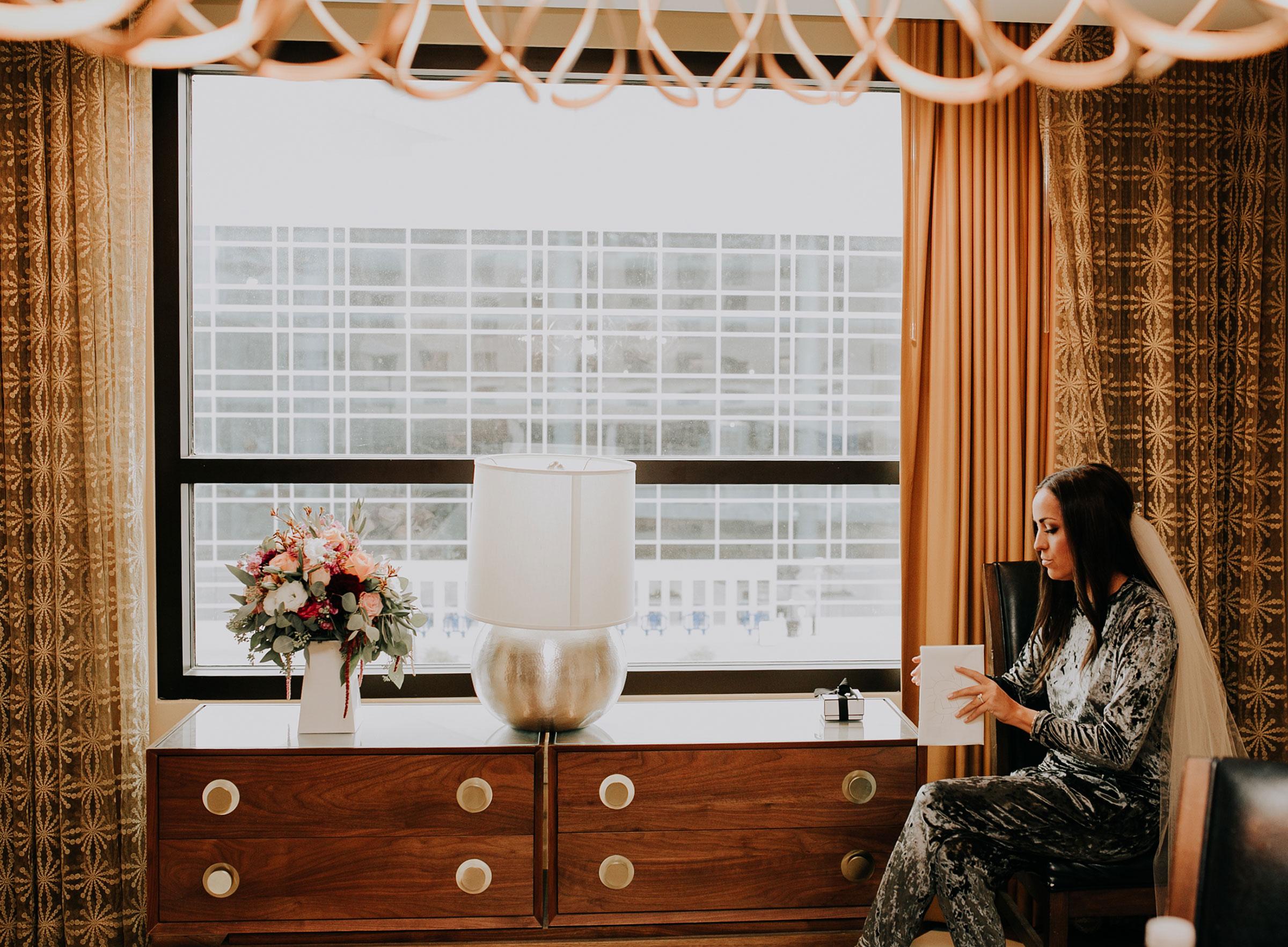 bride-opening-gift-from-groom-hilton-omaha-nebraska-raelyn-ramey-photography.jpg
