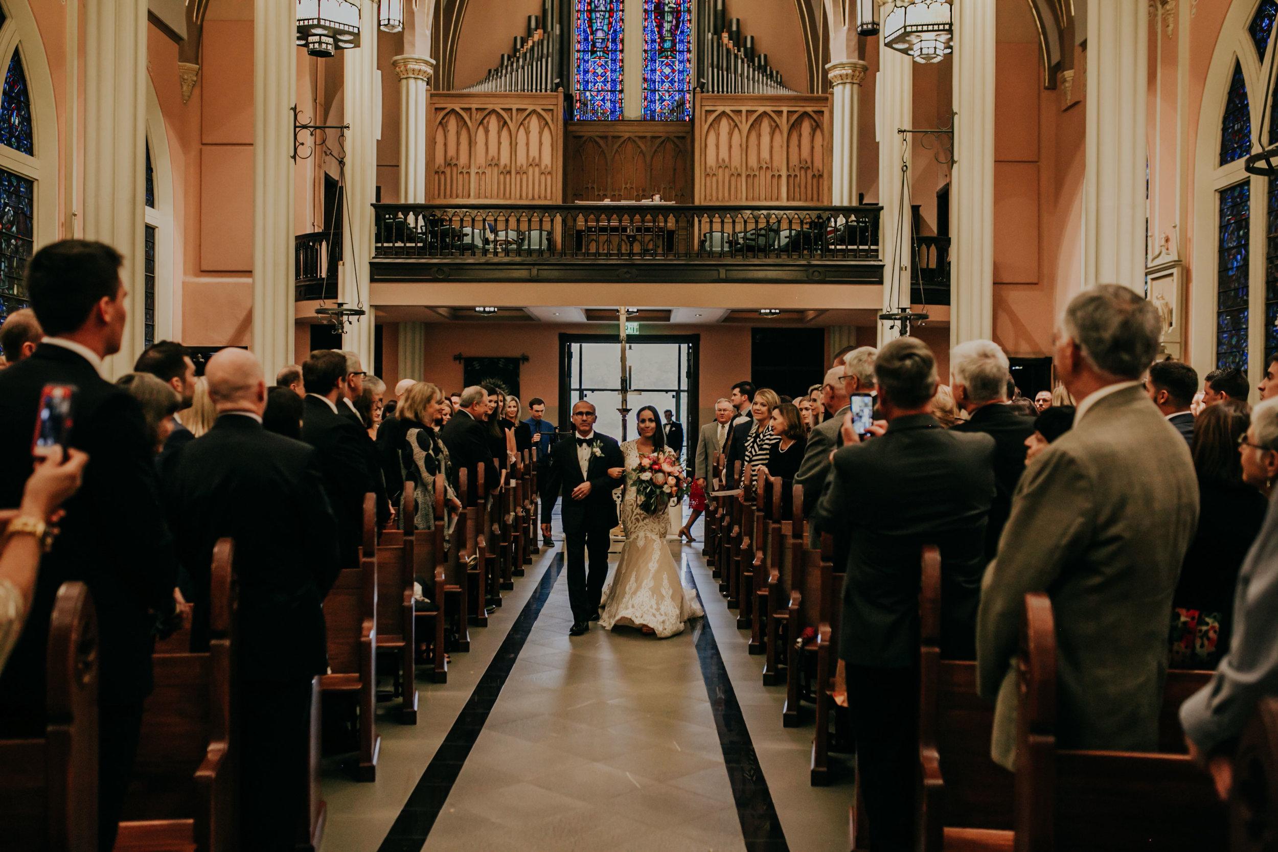 bride-walking-down-aisle-with-father-st-johns-church-at-creighton-omaha-nebraska-raelyn-ramey-photography.jpg
