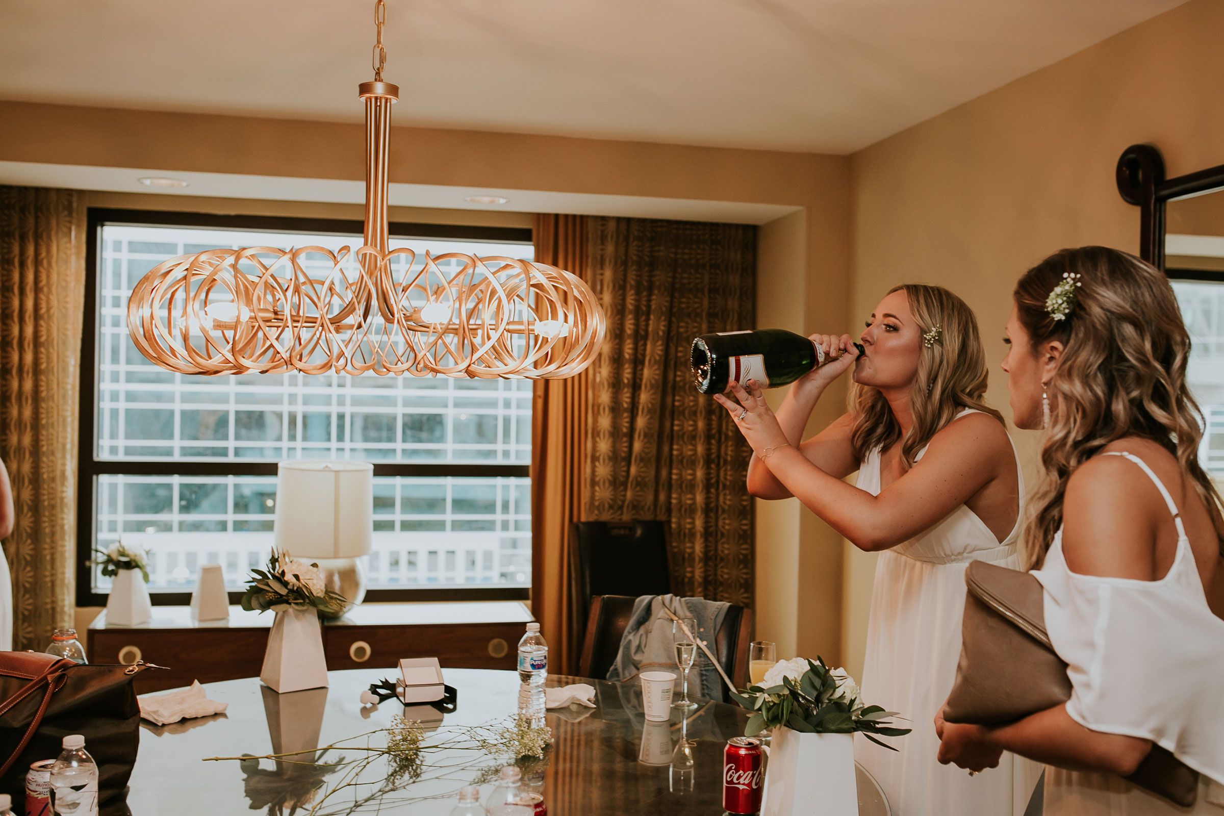bridesmaid-chugging-champagne-hilton-omaha-nebraska-raelyn-ramey-photography.jpg