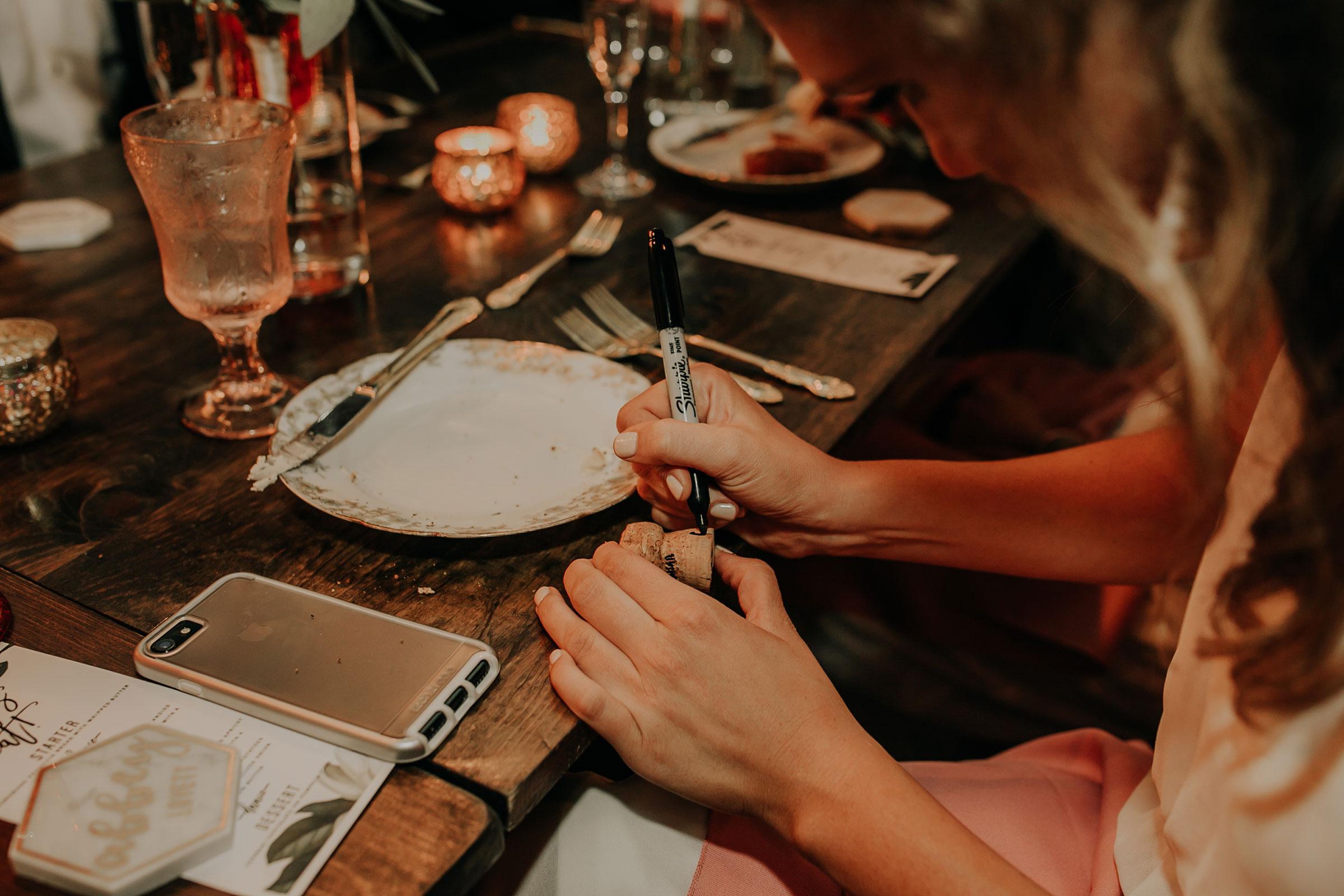 bridesmaid-signing-cork-for-wedding-couple-founders-one-nine-omaha-nebraska-raelyn-ramey-photography.jpg