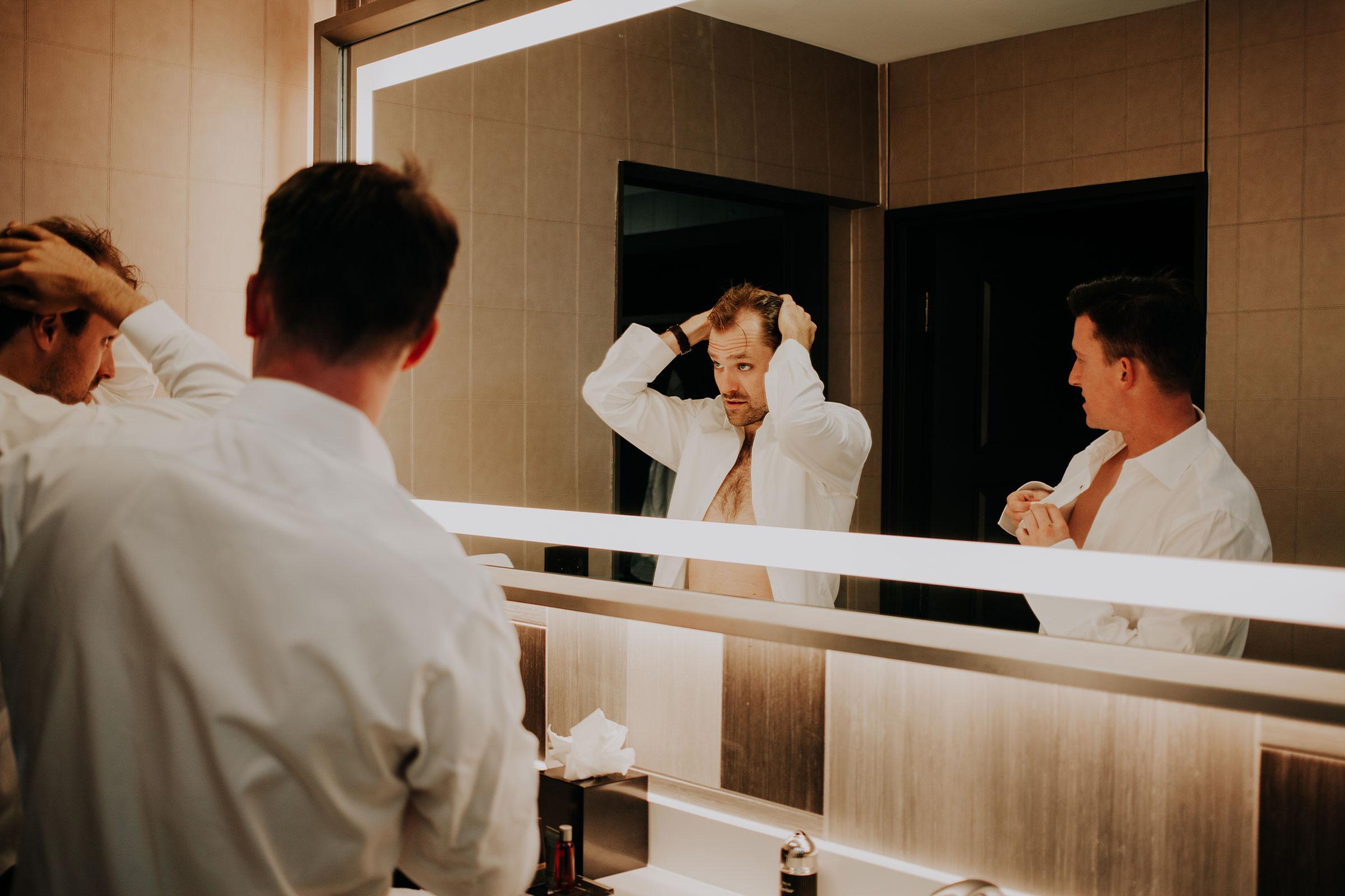 groom-and-groomsmen-getting-ready-in-mirror-hilton-omaha-nebraska-raelyn-ramey-photography.jpg