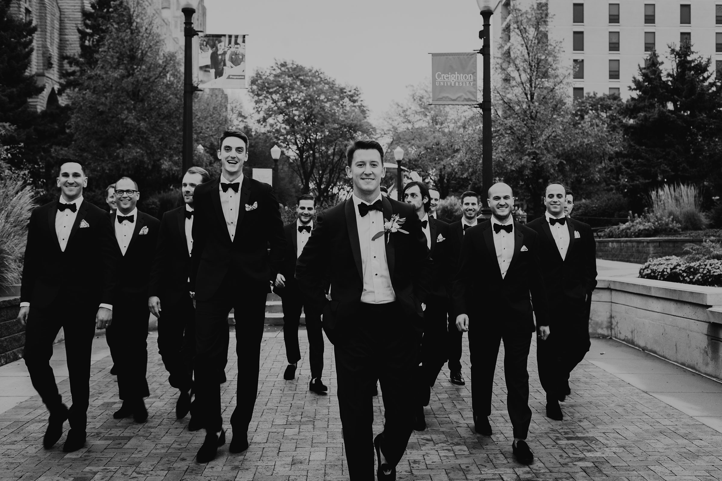 groom-and-groomsmen-walking-st-johns-church-at-creighton-omaha-nebraska-raelyn-ramey-photography.jpg