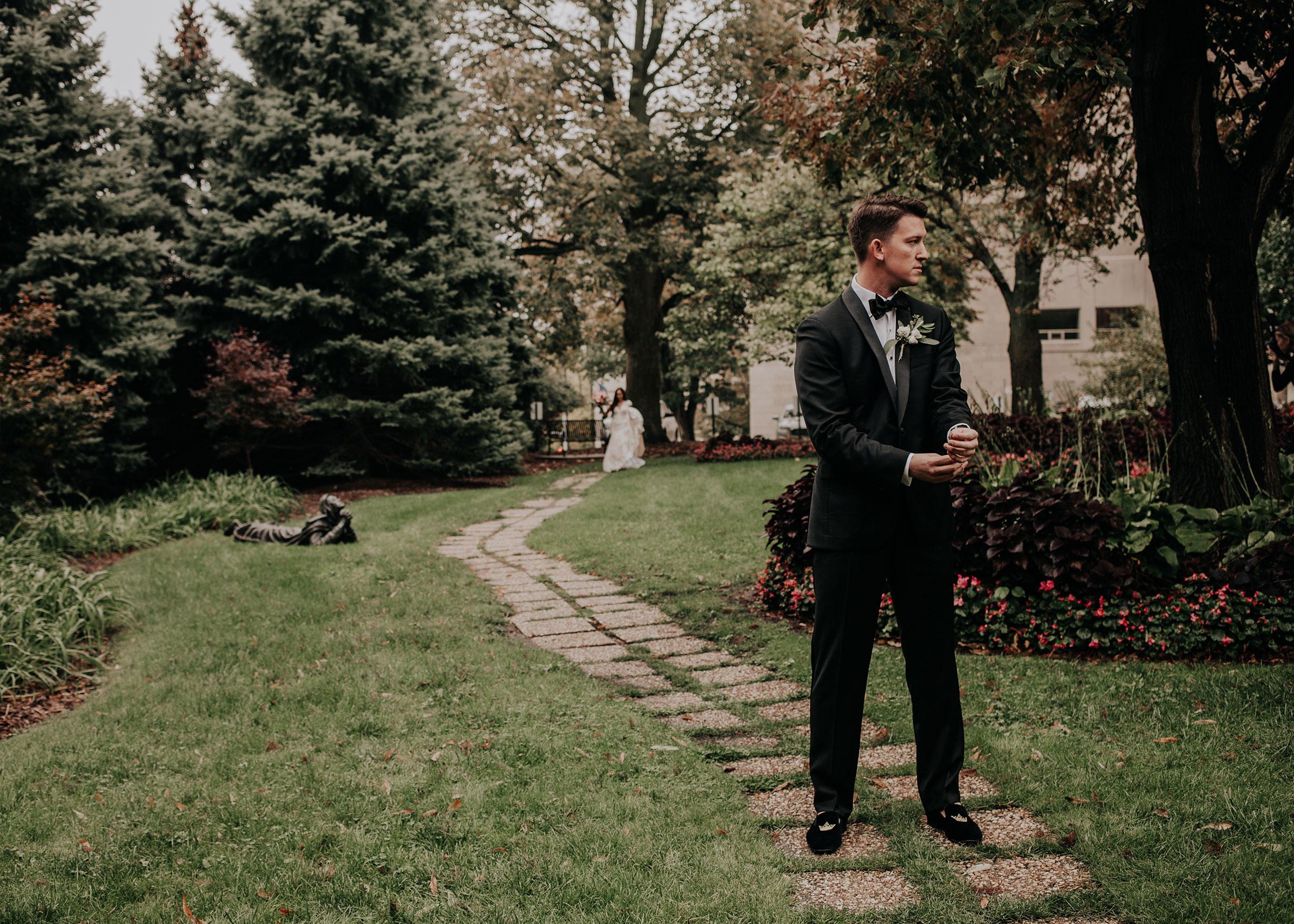 groom-waiting-for-bride-during-first-look-st-johns-church-at-creighton-omaha-nebraska-raelyn-ramey-photography.jpg