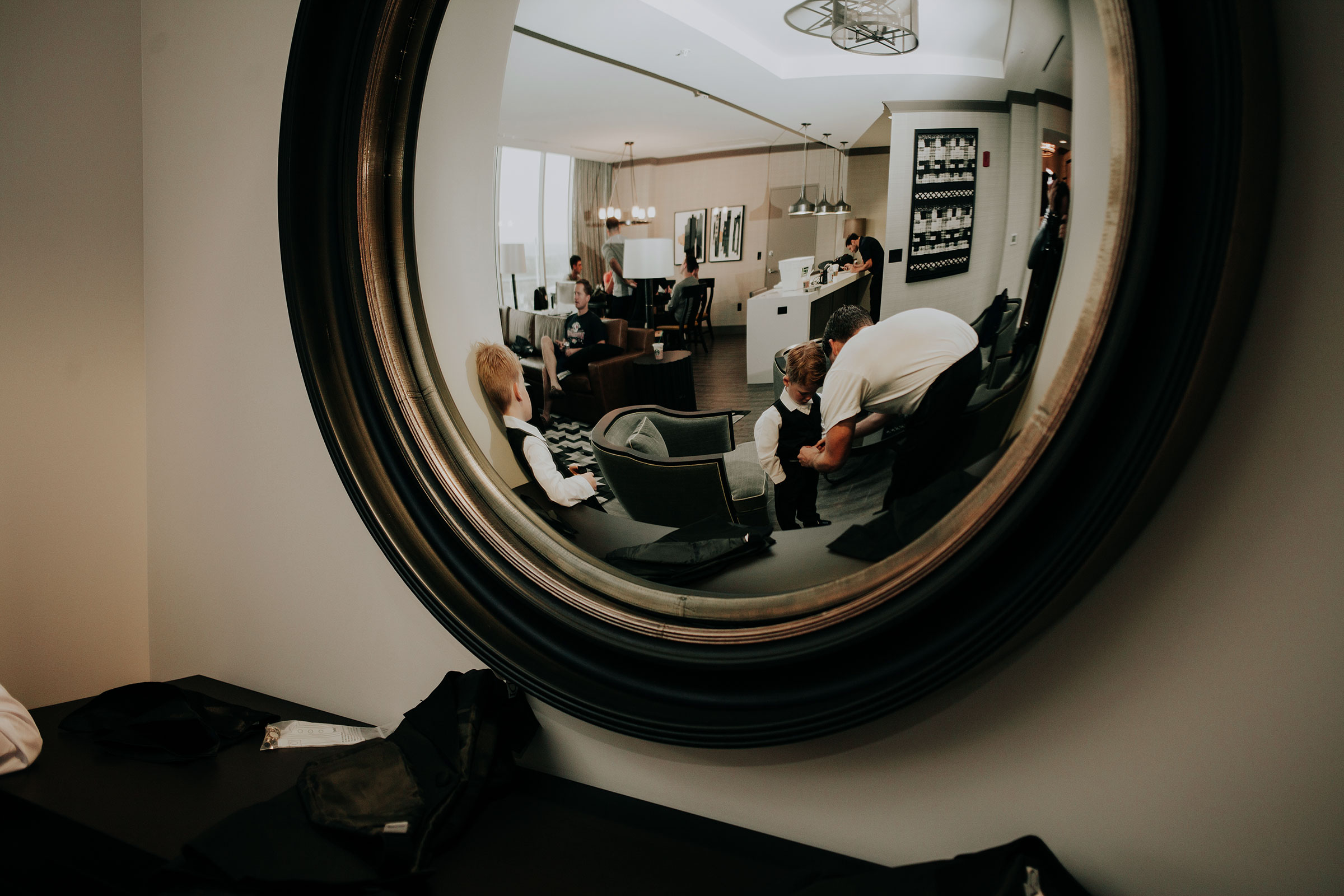 groomsmen-helping-kids-get-ready-through-mirror-hilton-omaha-nebraska-raelyn-ramey-photography.jpg
