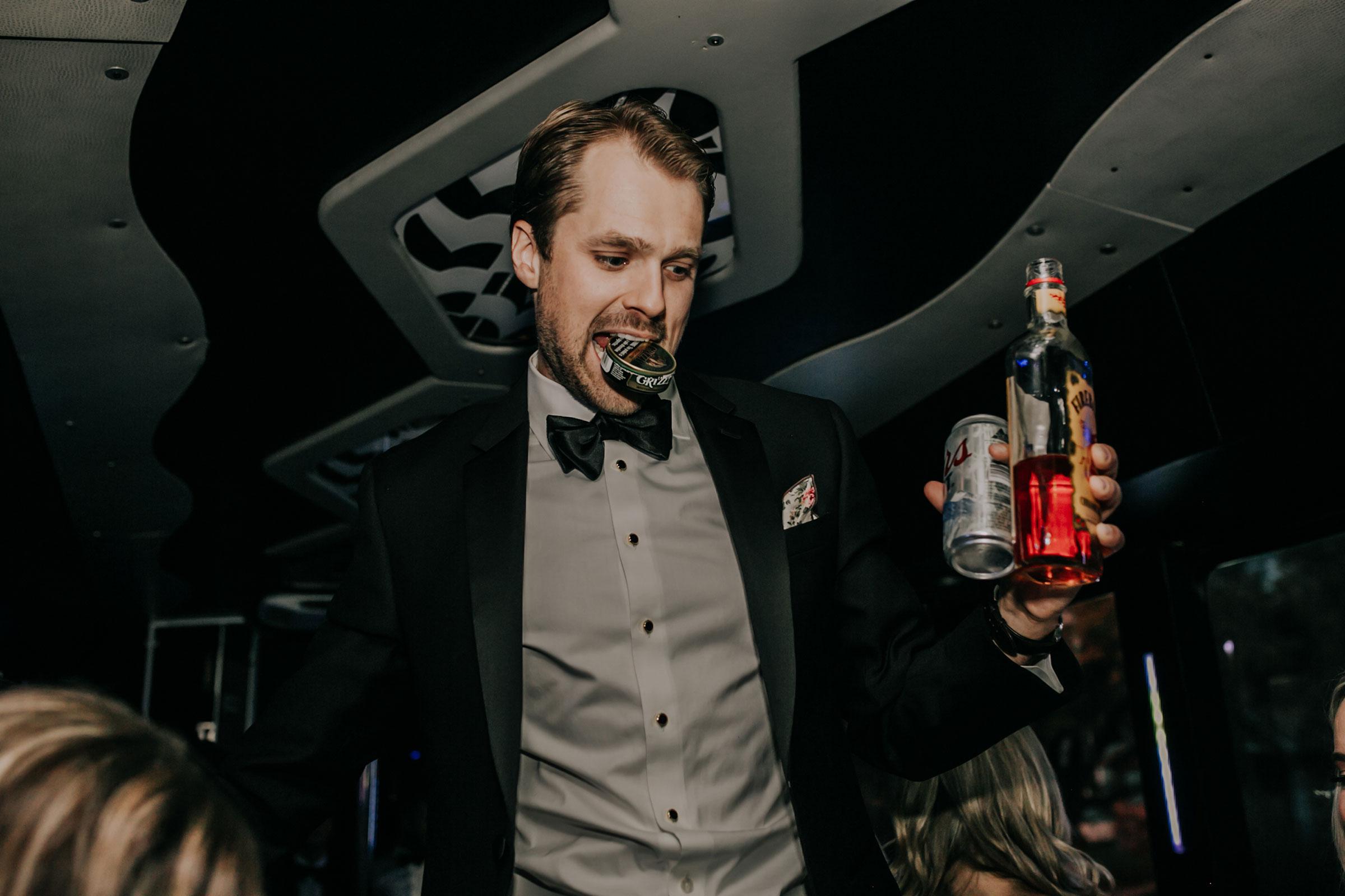 groomsmen-holding-fireball-chew-on-party-bus-omaha-nebraska-raelyn-ramey-photography.jpg