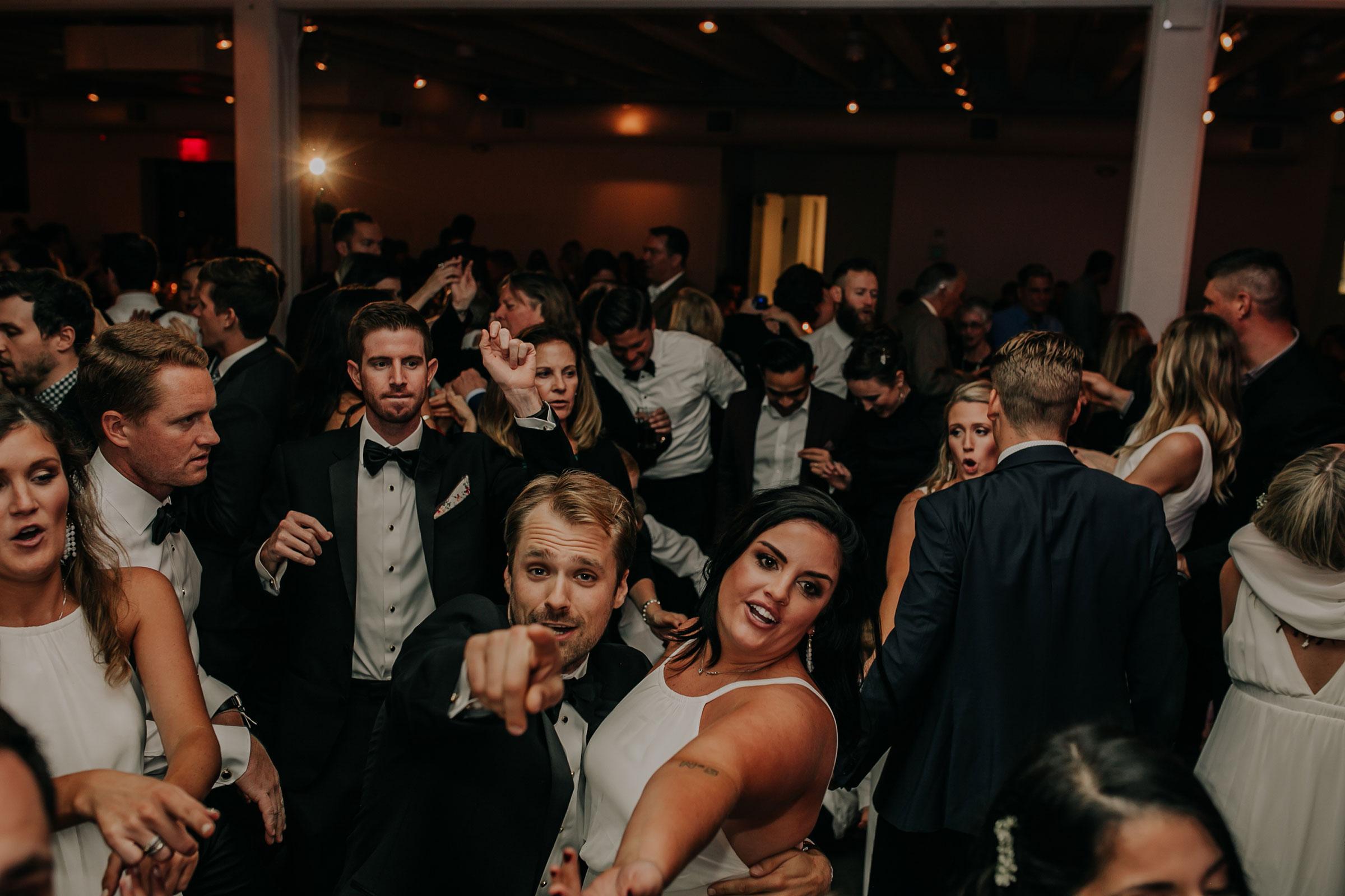 groomsmen-pointing-at-camera-while-dancing-founders-one-nine-omaha-nebraska-raelyn-ramey-photography.jpg