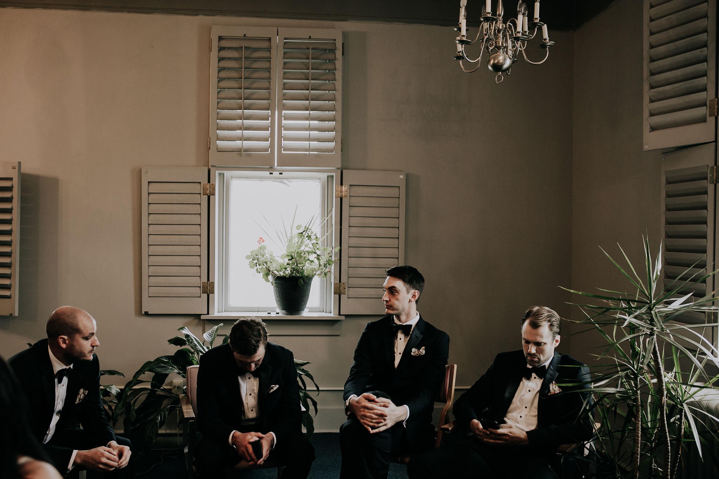 groomsmen-waiting-for-ceremony-to-start-st-johns-church-at-creighton-omaha-nebraska-raelyn-ramey-photography.jpg