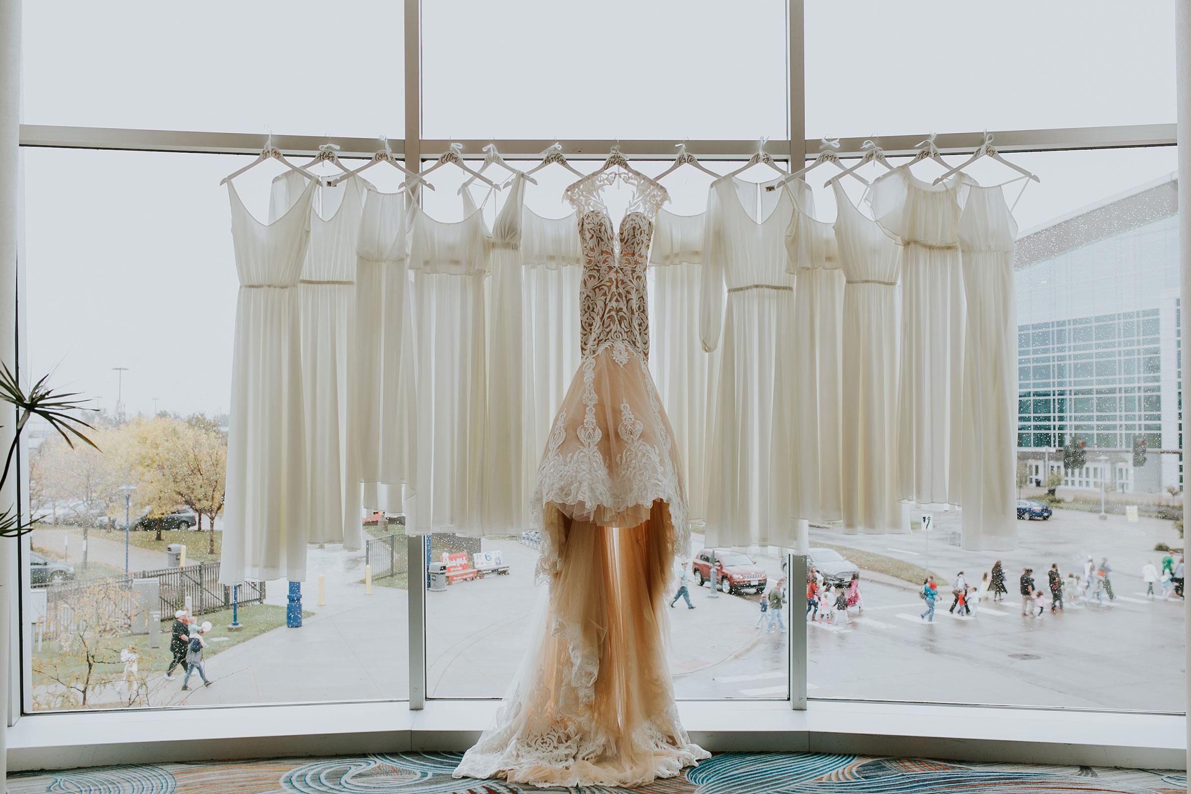 wedding-gown-and-bridesmaids-dresses-hanging-in-window-hilton-omaha-nebraska-raelyn-ramey-photography.jpg