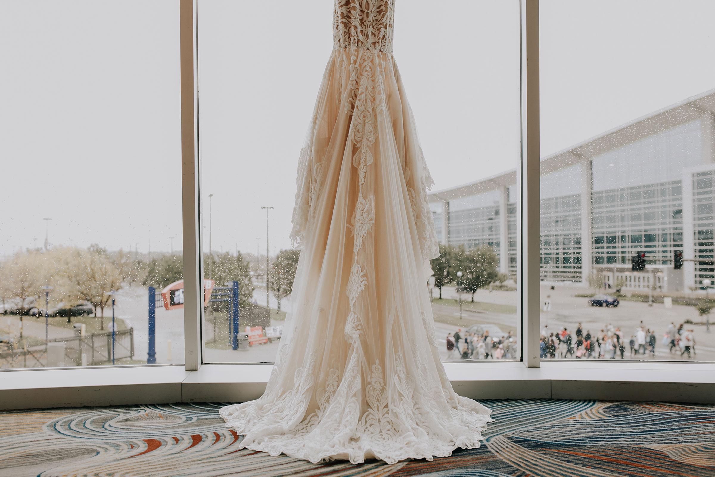 wedding-gown-back-hanging-in-window-hilton-omaha-nebraska-raelyn-ramey-photography.jpg