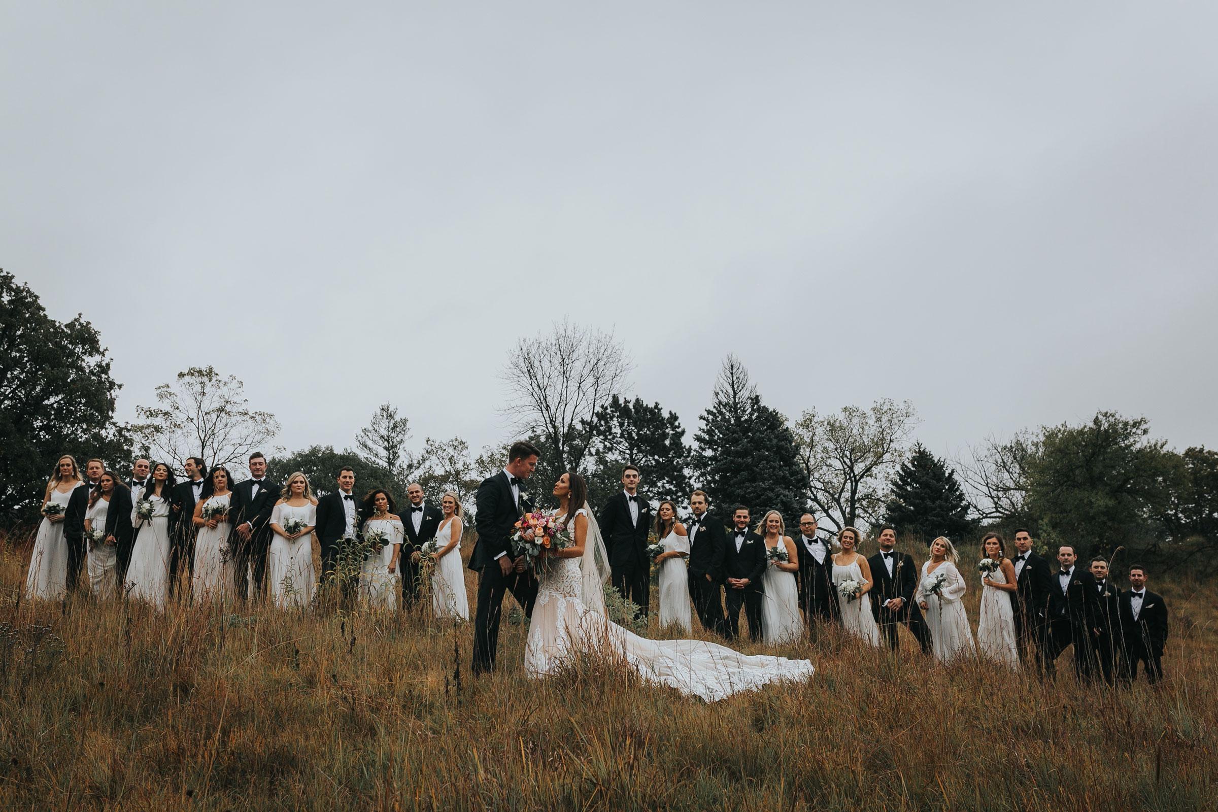 wedding-party-of-twelve-standing-on-hill-top-omaha-nebraska-raelyn-ramey-photography.jpg