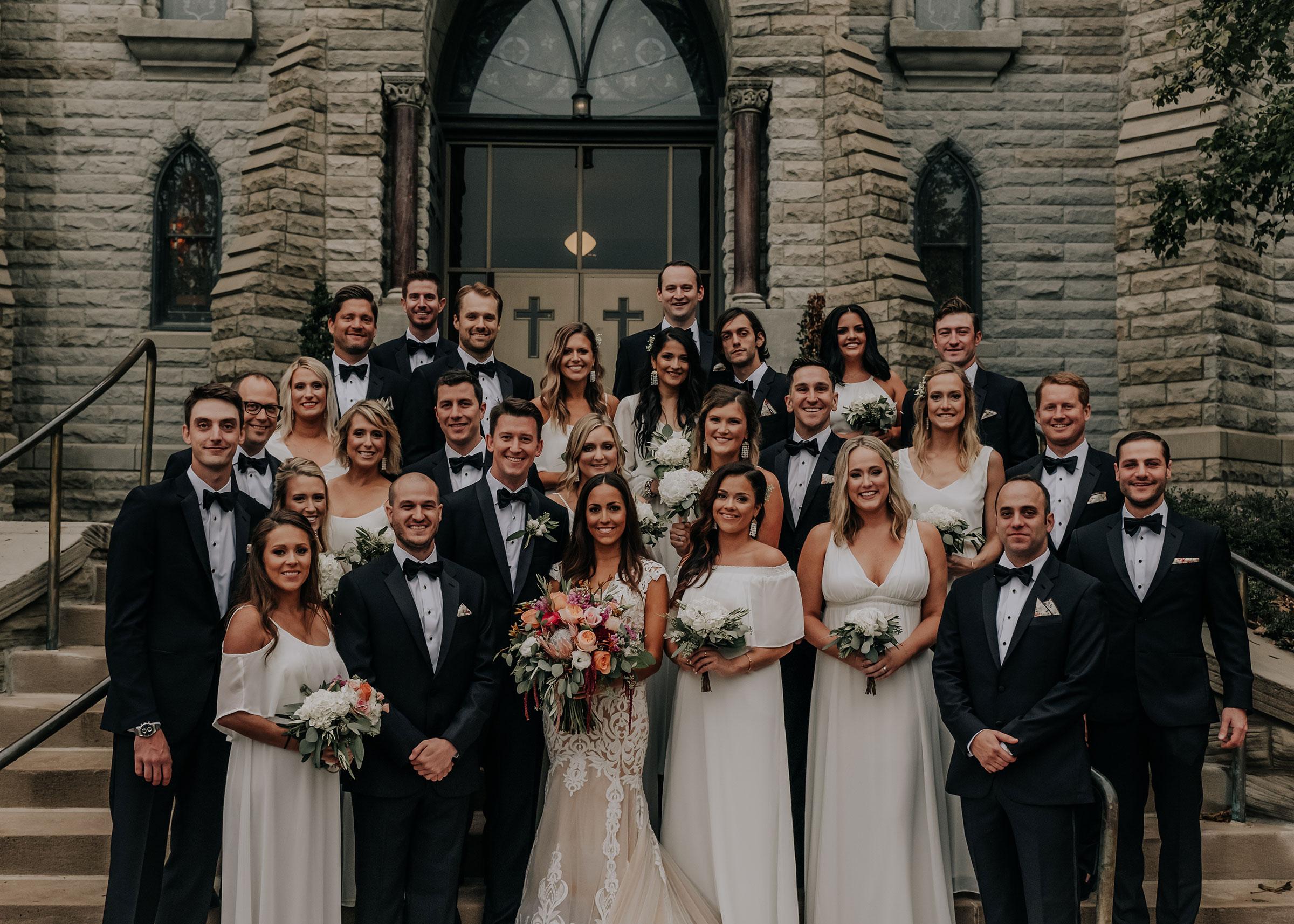 whole-wedding-party-posing-on-stairs-st-johns-church-at-creighton-omaha-nebraska-raelyn-ramey-photography.jpg