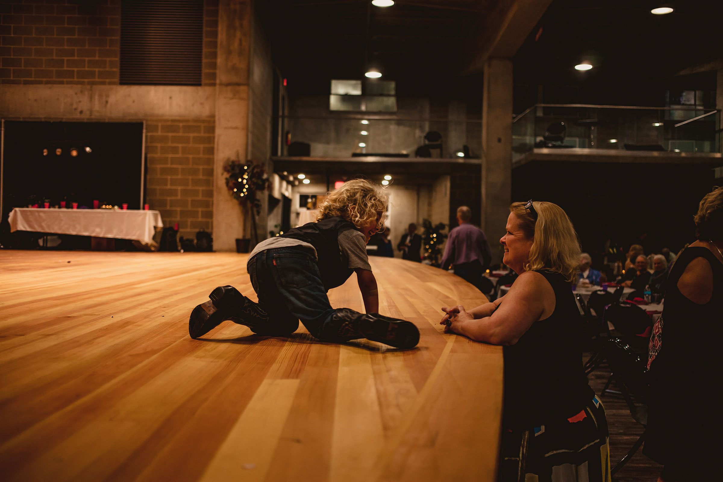 boy-playing-on-stage-talking-to-mother-at-reception-pella-plaza-desmoines-iowa-raelyn-ramey-photography.jpg