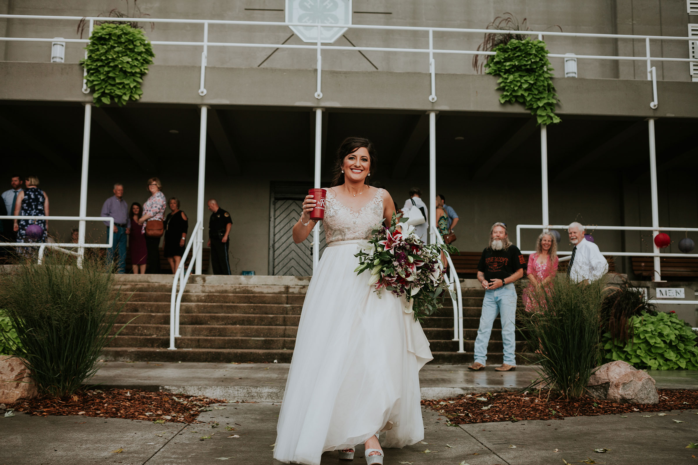 bride-holding-a-drink-and-running-to-party-bus-iowa-state-fairgrounds-desmoines-iowa-raelyn-ramey-photography.jpg