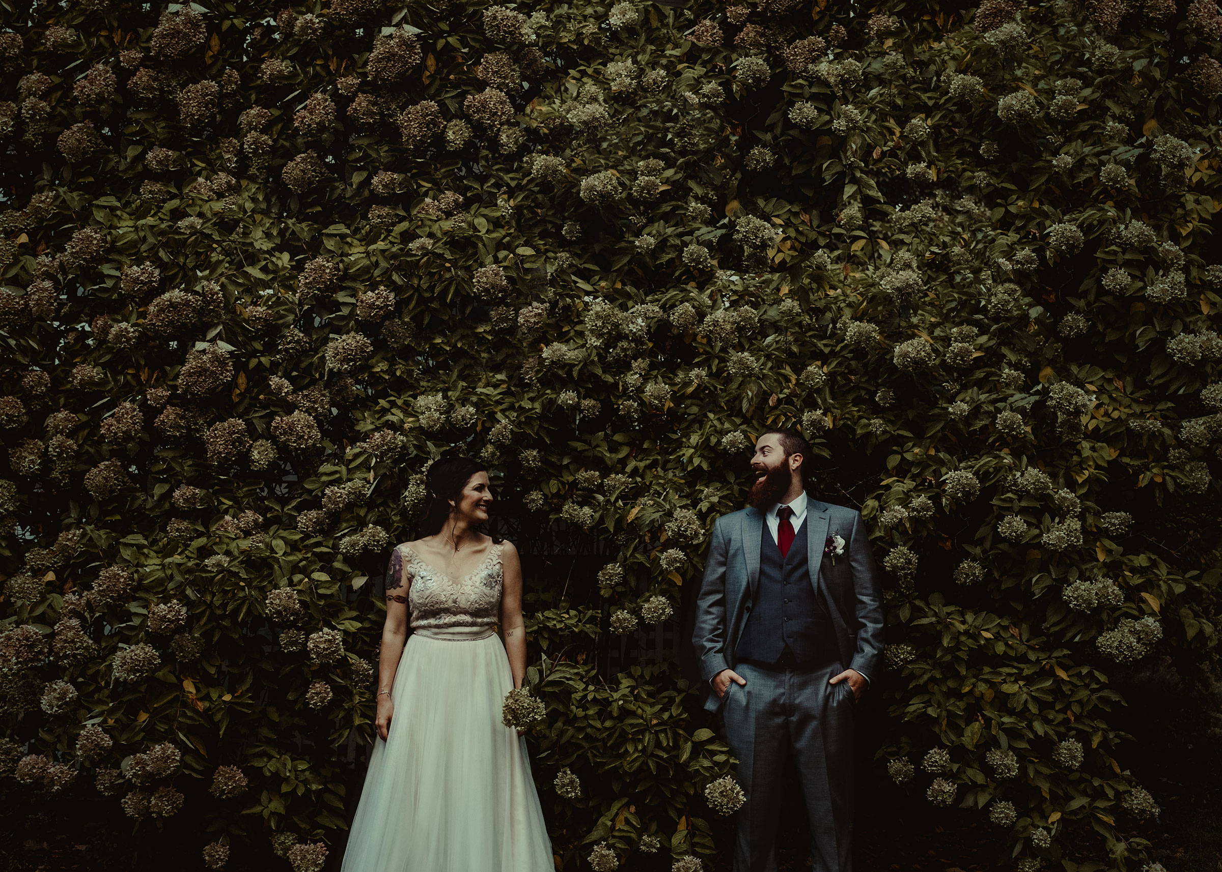 bride-groom-looking-at-each-other-in-front-of-flowers-iowa-state-fairgrounds-desmoines-iowa-raelyn-ramey-photography.jpg