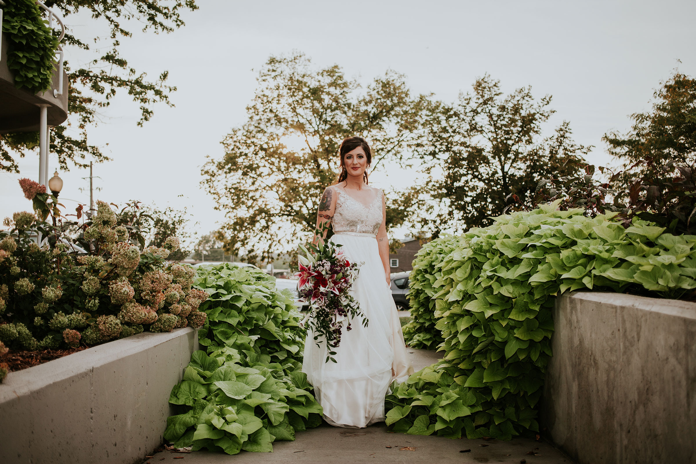 bride-standing-amoung-plants-pella-plaza-desmoines-iowa-raelyn-ramey-photography.jpg