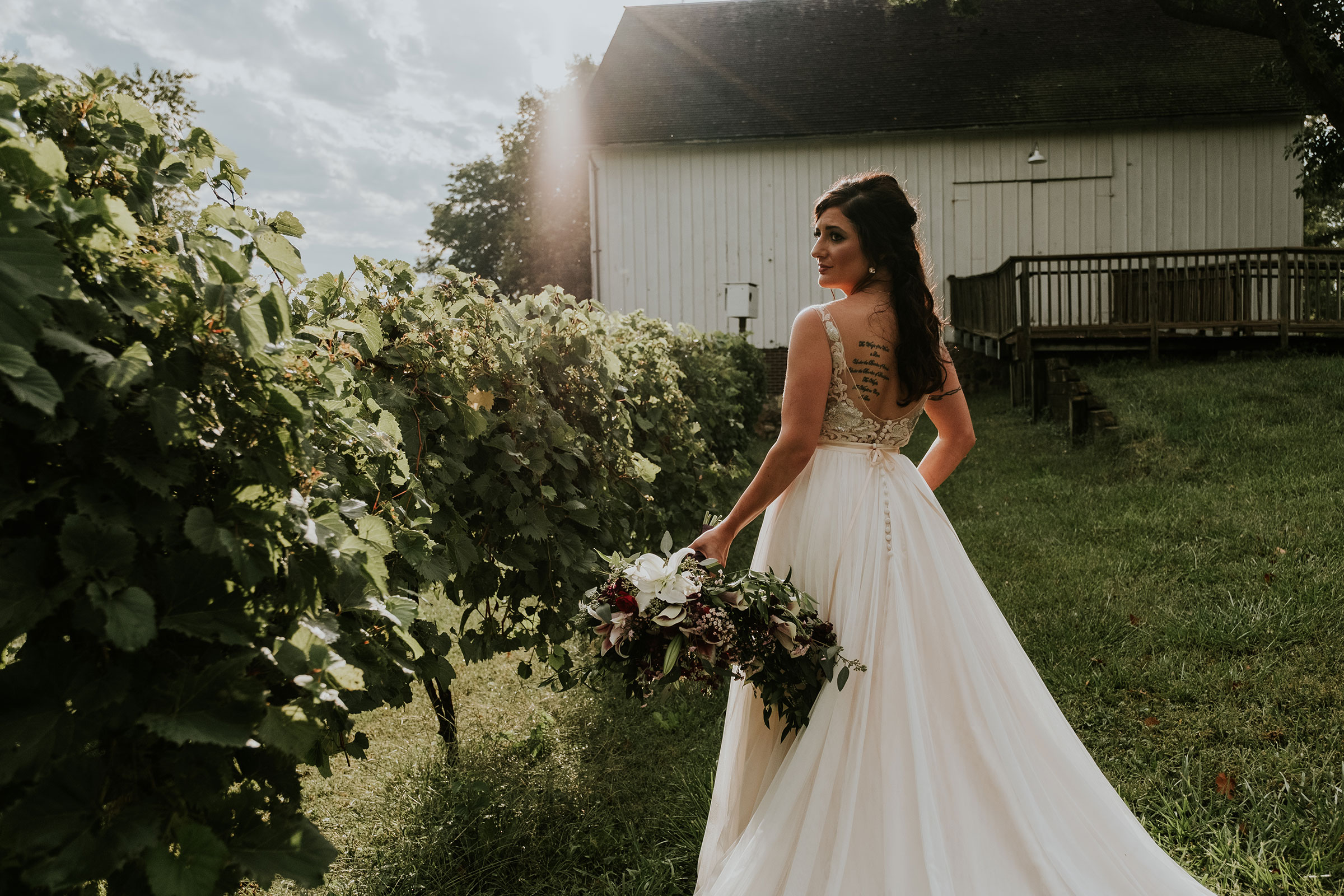 bride-standing-next-to-grape-vines-iowa-state-fairgrounds-desmoines-iowa-raelyn-ramey-photography.jpg
