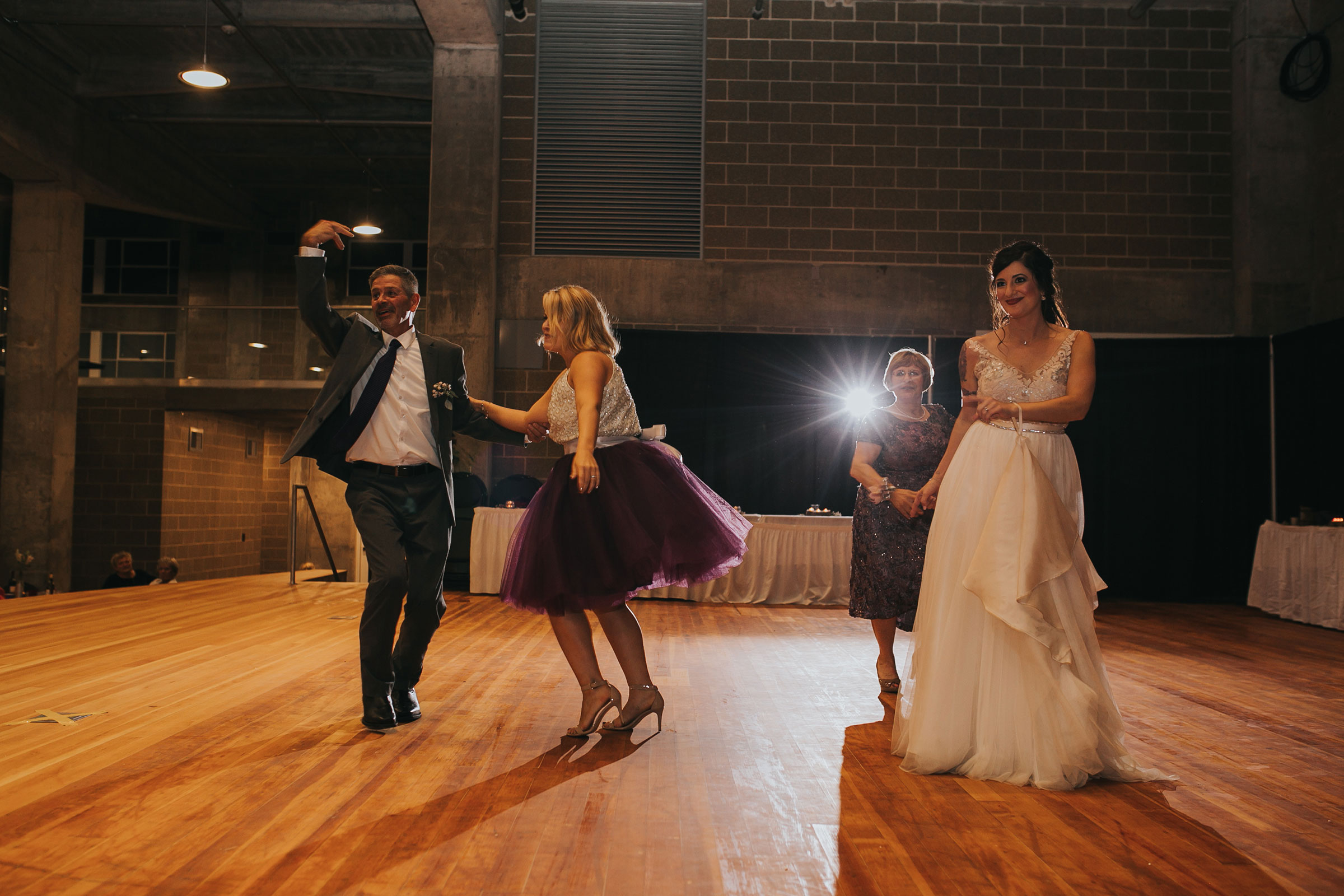 brides-first-dance-with-family-at-reception-pella-plaza-desmoines-iowa-raelyn-ramey-photography.jpg