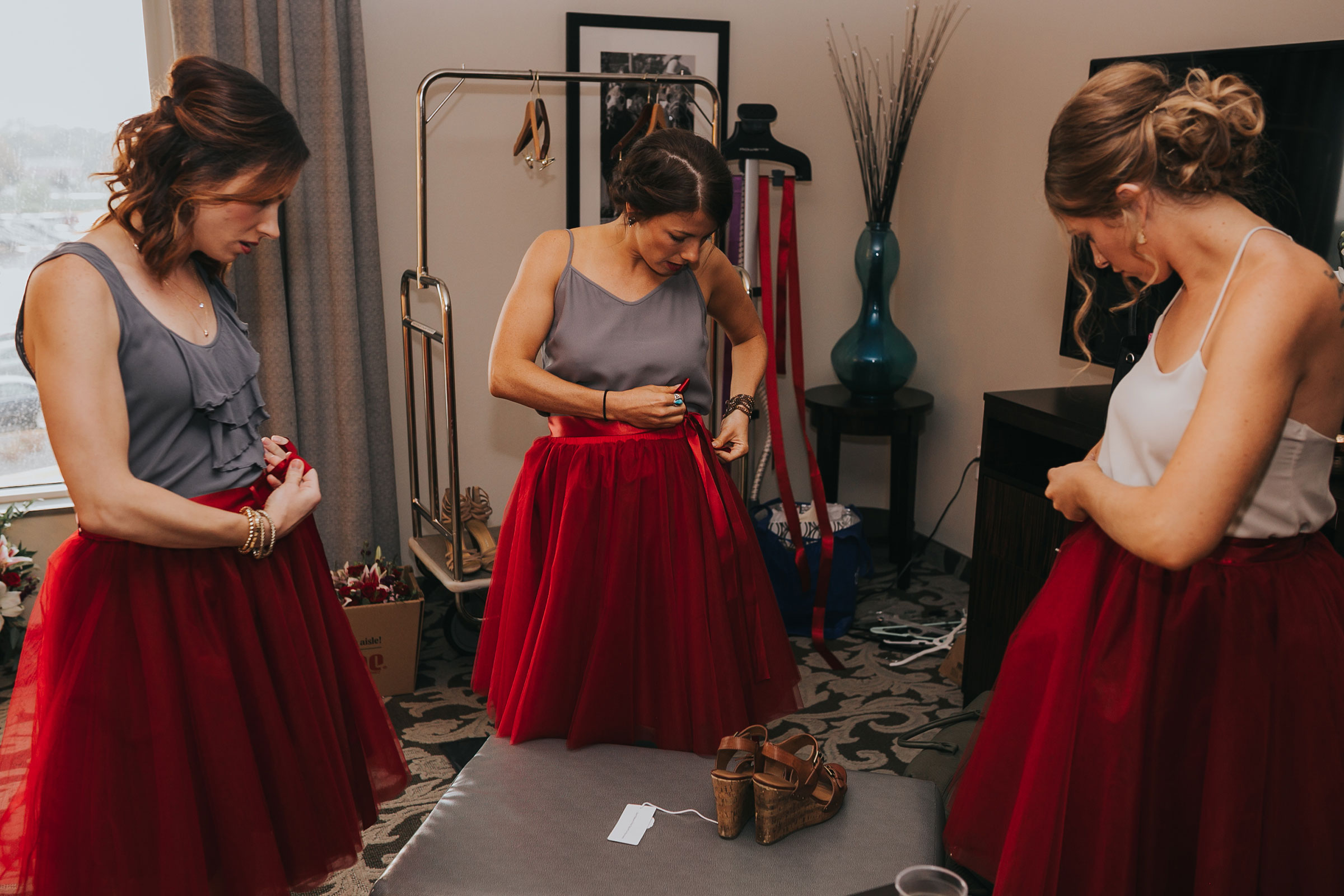 bridesmaids-putting-skirts-on-prairie-meadows-desmoines-iowa-raelyn-ramey-photography.jpg