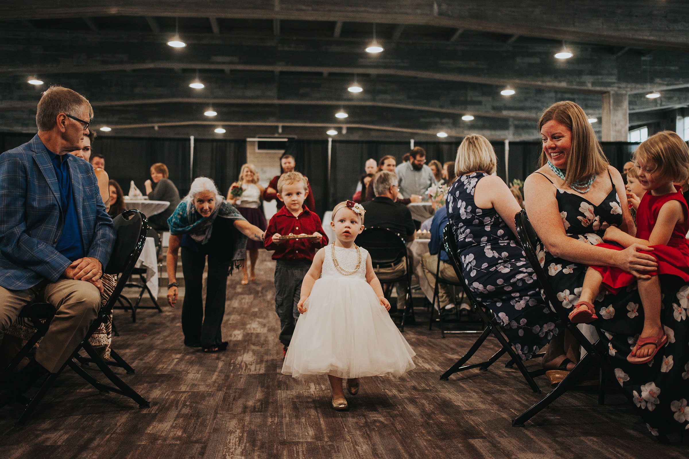 flower-girl-walking-down-aisle-pella-plaza-desmoines-iowa-raelyn-ramey-photography.jpg